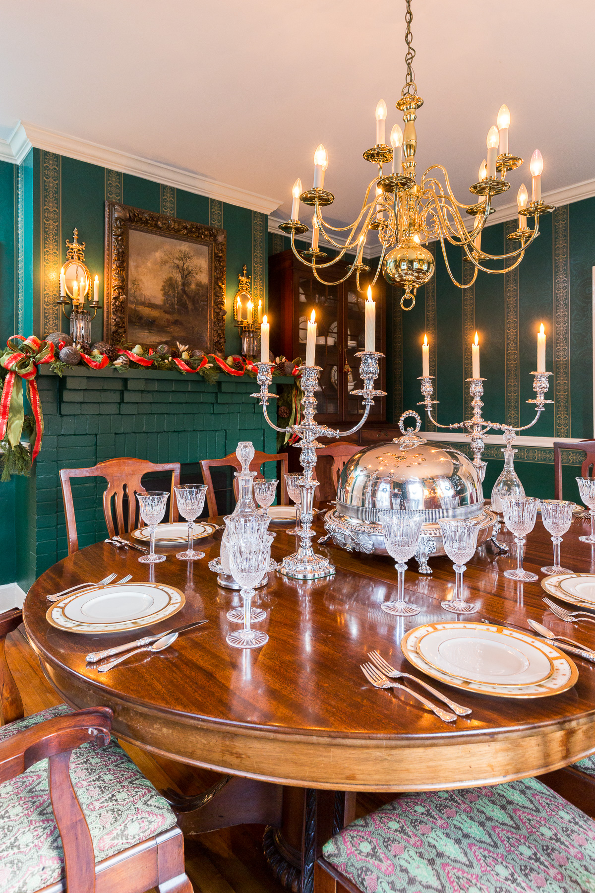A formal elegant dining room with dark green walls is decorated for the holidays by Reed & Acanthus Interior Design