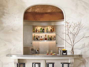 "Find the Right Finishes. ""A bar is about showing off,"" says Wesley Moon. ""You could keep your liquor and glasses hidden in a cabinet, but you've decided to put them on display. Give guests something to talk about. Pick a cabinet finish that's a bit unusual or use a stone for the counter that's rare and special.""   In this space, Moon uses a textured eglomise glass for the upper cabinet doors and backsplash, which are framed by woodwork with a metallic lacquer finish. To add drama, the domed ceiling is covered in gold-leaf mosaic tile."