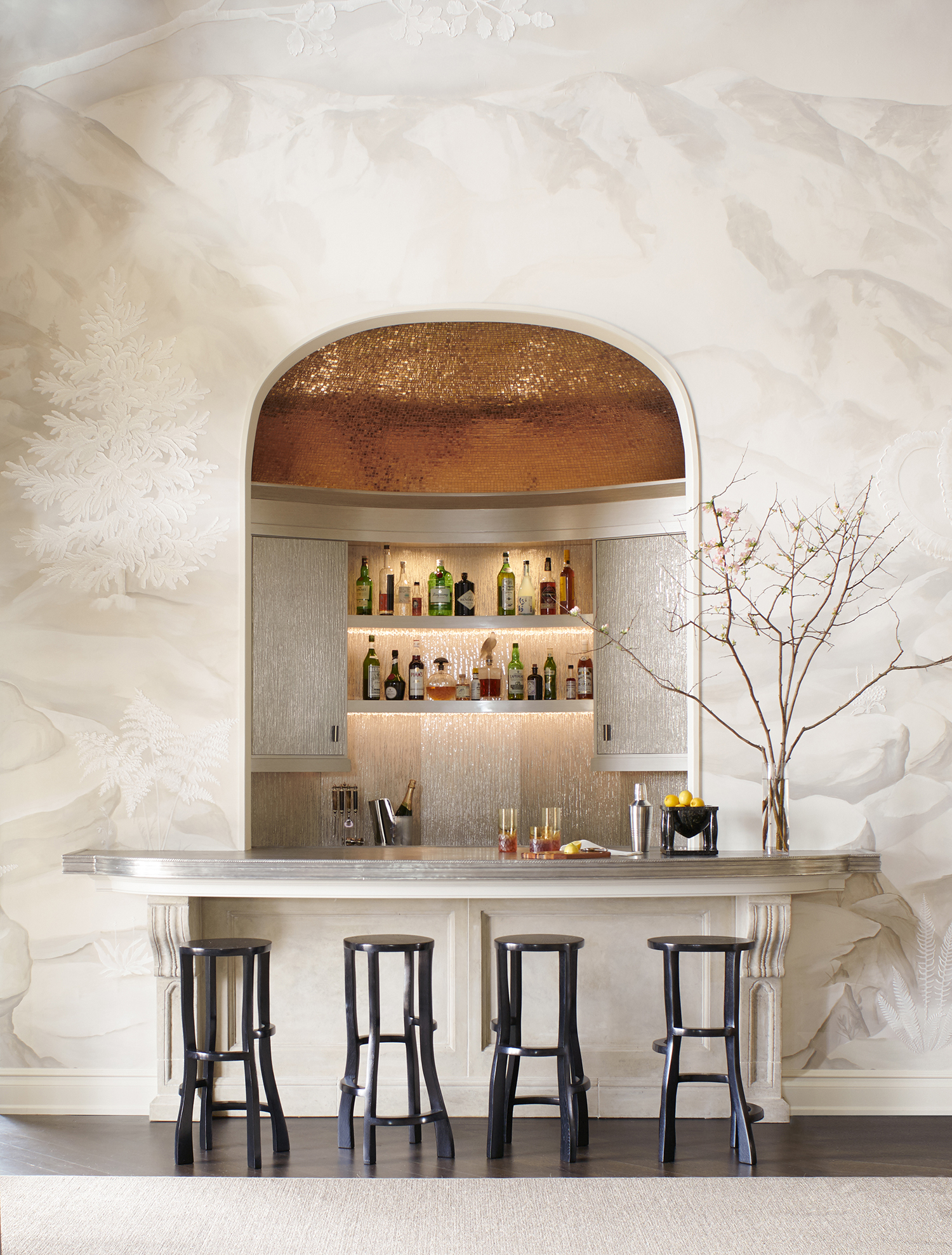"""Find the Right Finishes. """"A bar is about showing off,"""" says Wesley Moon. """"You could keep your liquor and glasses hidden in a cabinet, but you've decided to put them on display. Give guests something to talk about. Pick a cabinet finish that's a bit unusual or use a stone for the counter that's rare and special.""""   In this space, Moonusesa textured eglomise glass forthe upper cabinet doors and backsplash, which are framed by woodwork with a metallic lacquer finish. To add drama,the domed ceiling is covered in gold-leaf mosaic tile."""