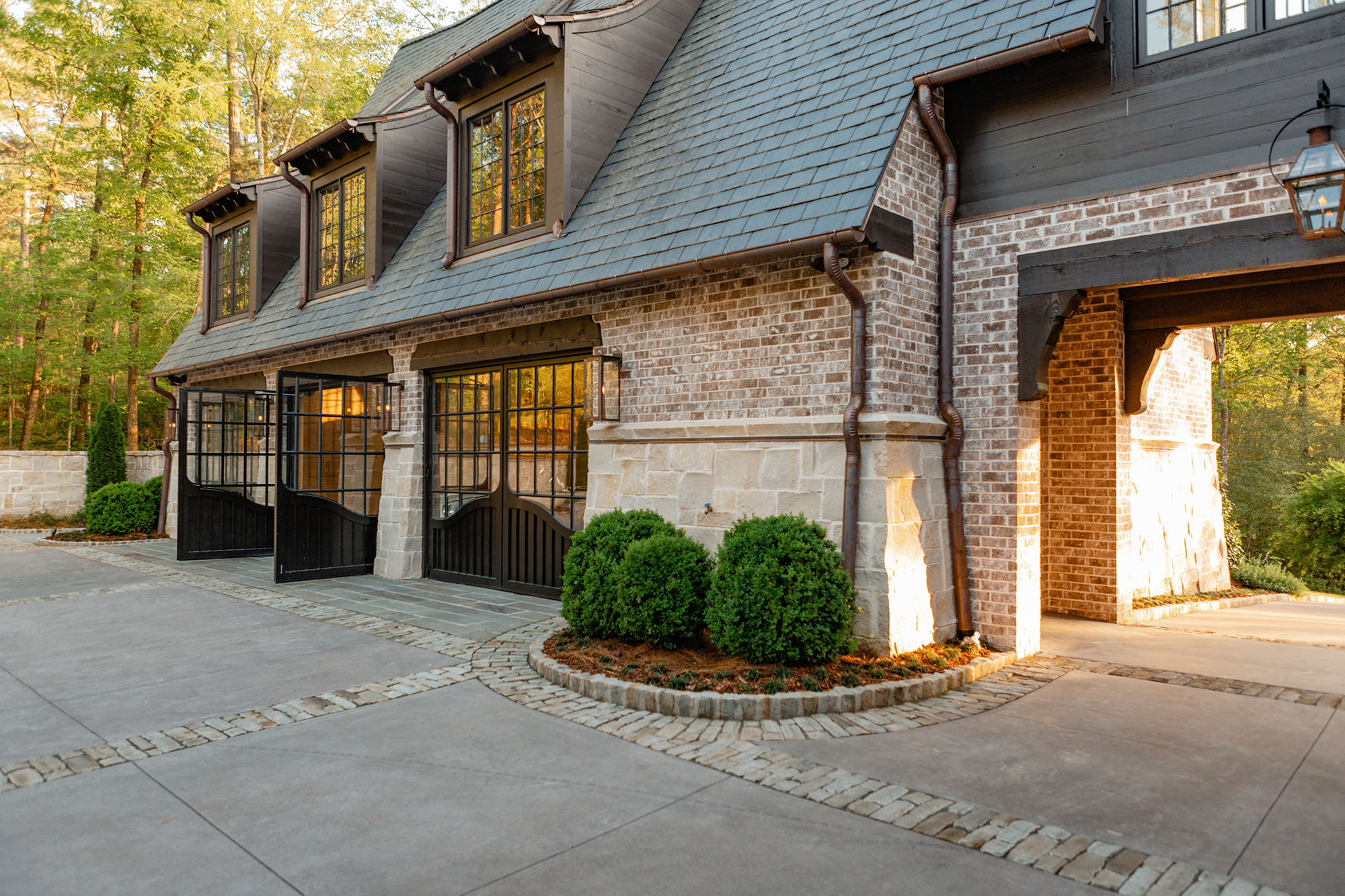 "In their architectural work, the team at Christopher Architecture & Interiors saw the need to add a sense of luxury to a previously overlooked part of the home: garage doors. They developed tailor-made, out-swinging carriage garage doors which have side hinges, enabling them to function like larger front doors. With eight standard designs in the Bespoke Forged line, they can also customize the doors to match any home's style. Their doors even have the option of a ""man door,"" offering a section of the door that will open just for a person to walk through without having to open the entire unit."