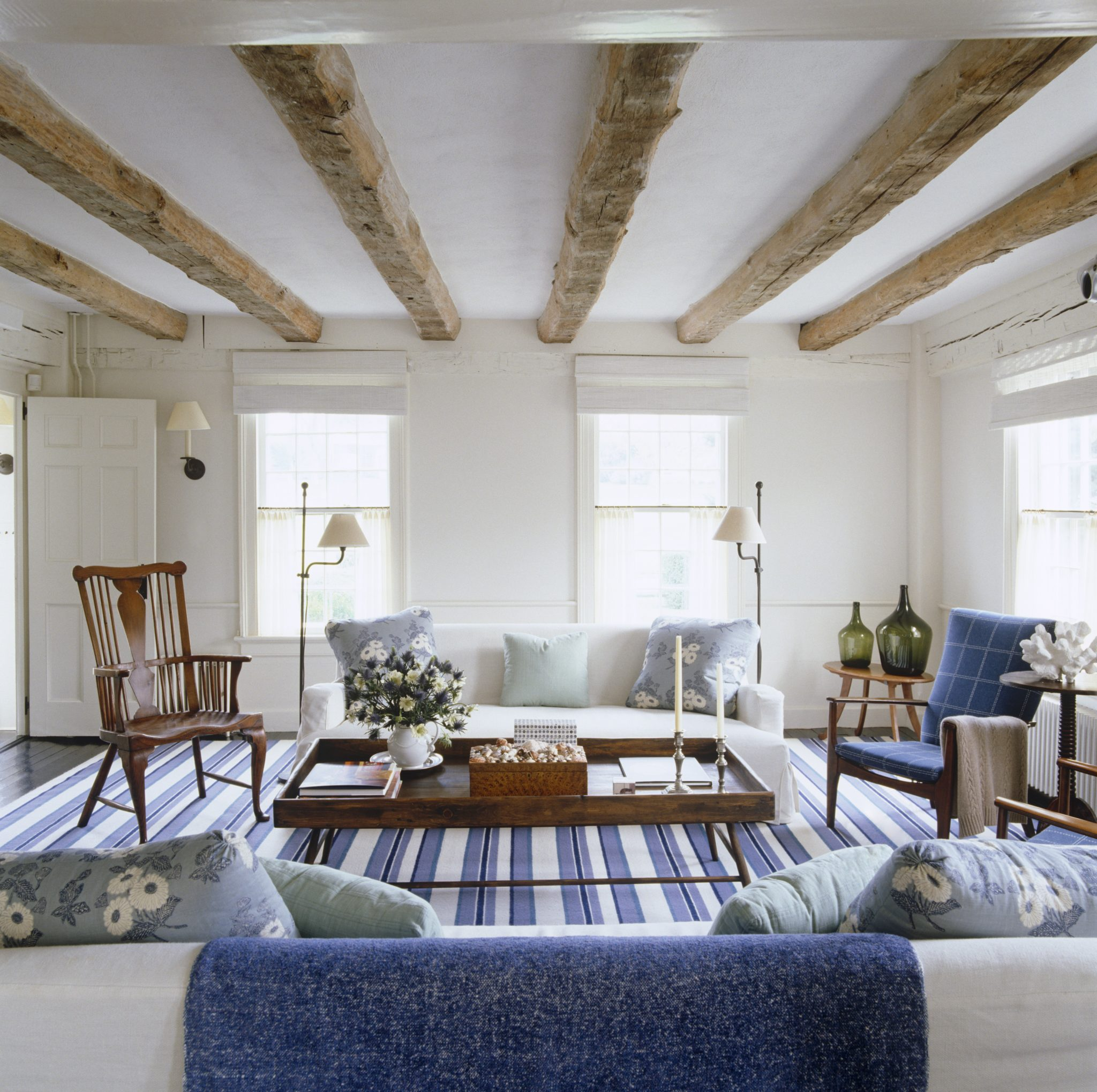 In a 230-year-old shingled house in East Hampton, the designer fitted out the living room with a new dhurrie carpet that lends it a fresh and beachy air. The blue stripes echo the antique beamed ceiling and add to the range of various blues throughout the house.