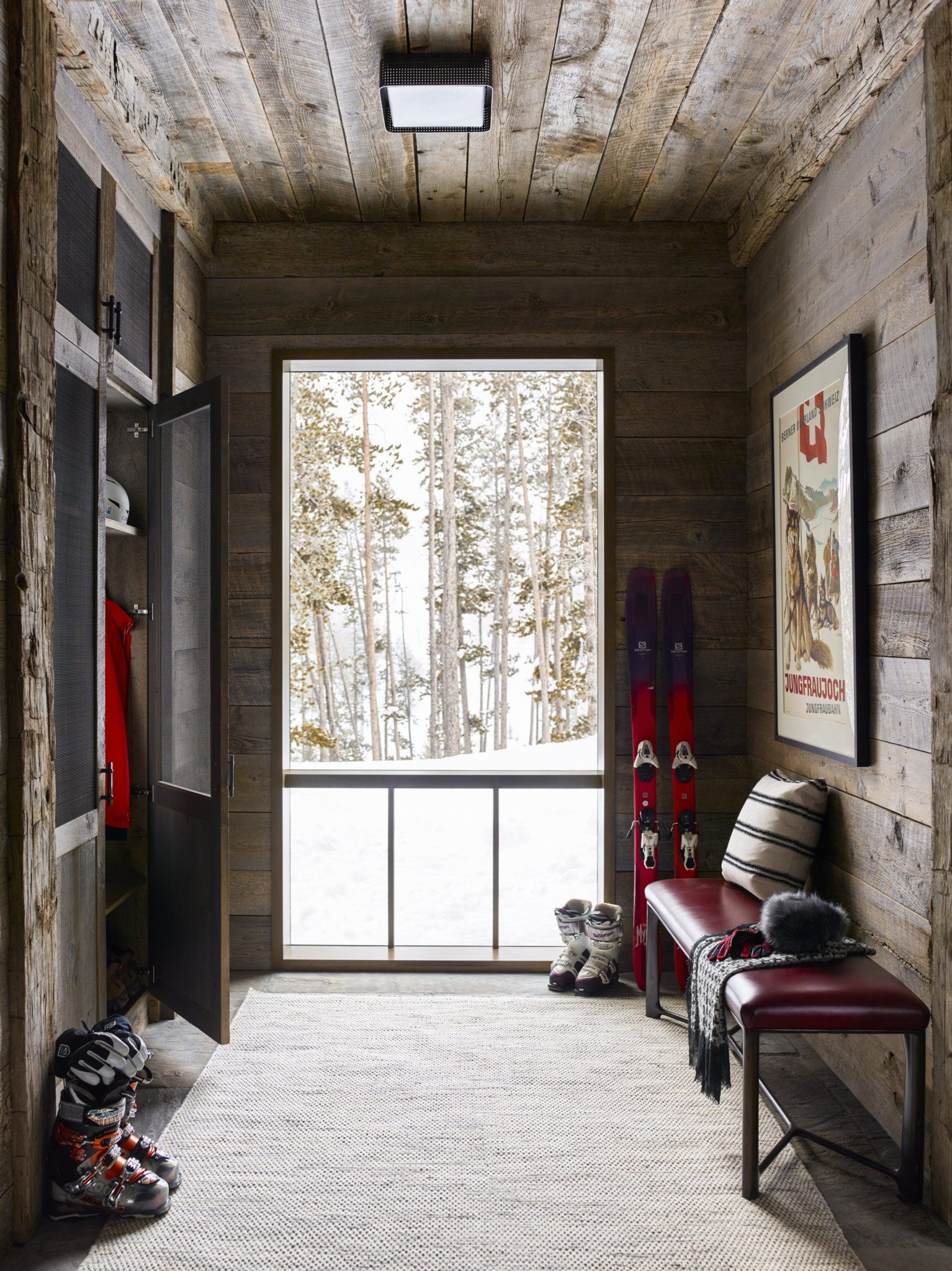 From the moment you enter the home, you are greeted by reclaimed wood walls and ceilings — which are present in much of the ski chalet's interior. A great place for storing ski gear and a winter wardrobe, the entryway is full of custom, built-in cabinetry. After a long day on the mountain, the family can rest their scarves or gloves on the sleek, bronze bench near the door. The bench is upholstered in Townsend leather, and decorated with a pillow in Schumacher fabric. To complete the design of the space, Shintaffer uses a surface mount from Circa Lighting, a vintage poster from Antikbar, and a wool tweed rug from Stacy Logan.