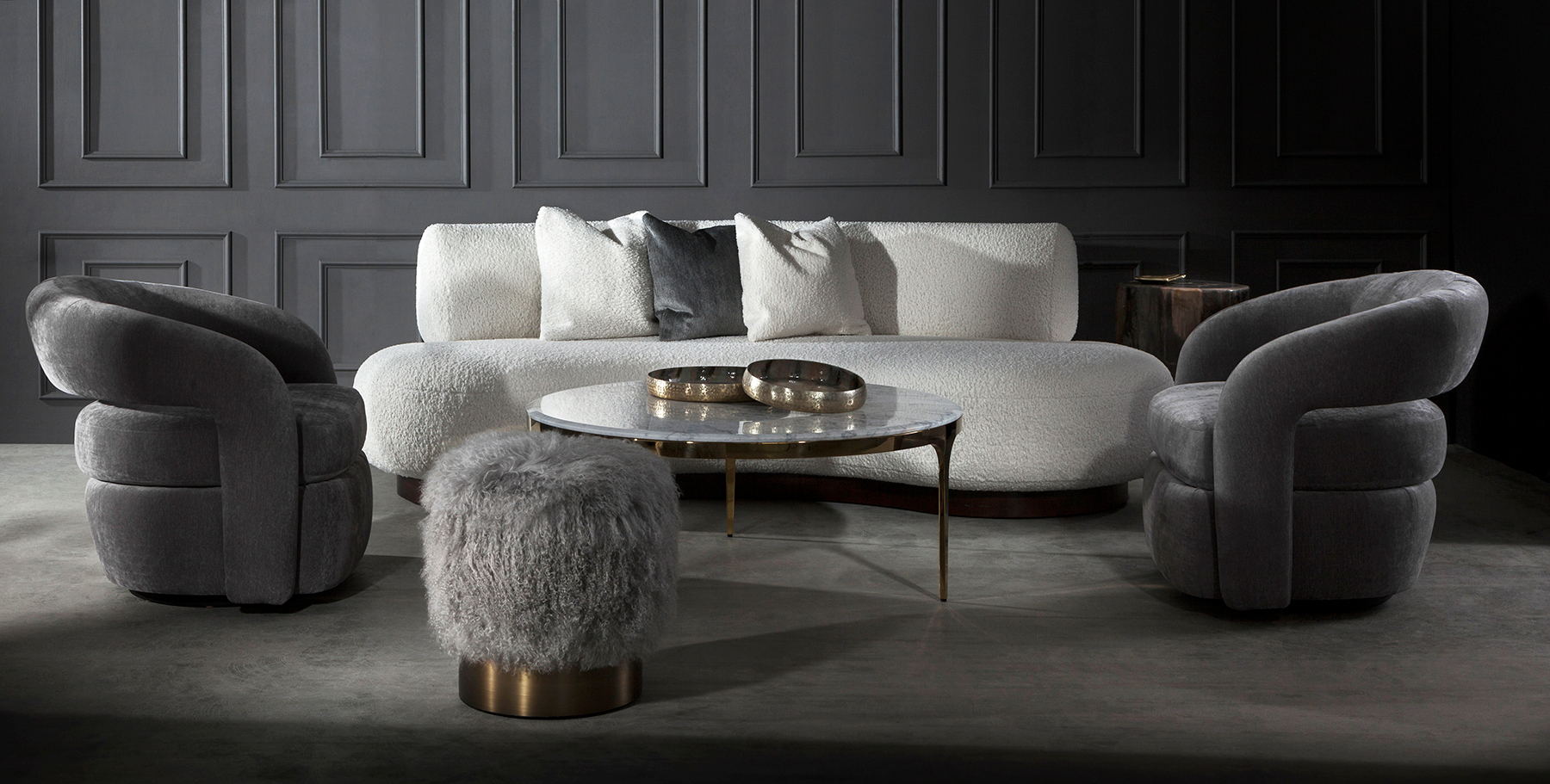 Curved sofas and chairs will be top of mind, along with comfort fabrics like shearling and richly textured surfaces. On either side of the photo are a pair of Targa Chairs, with a Doutzen Stool in front.