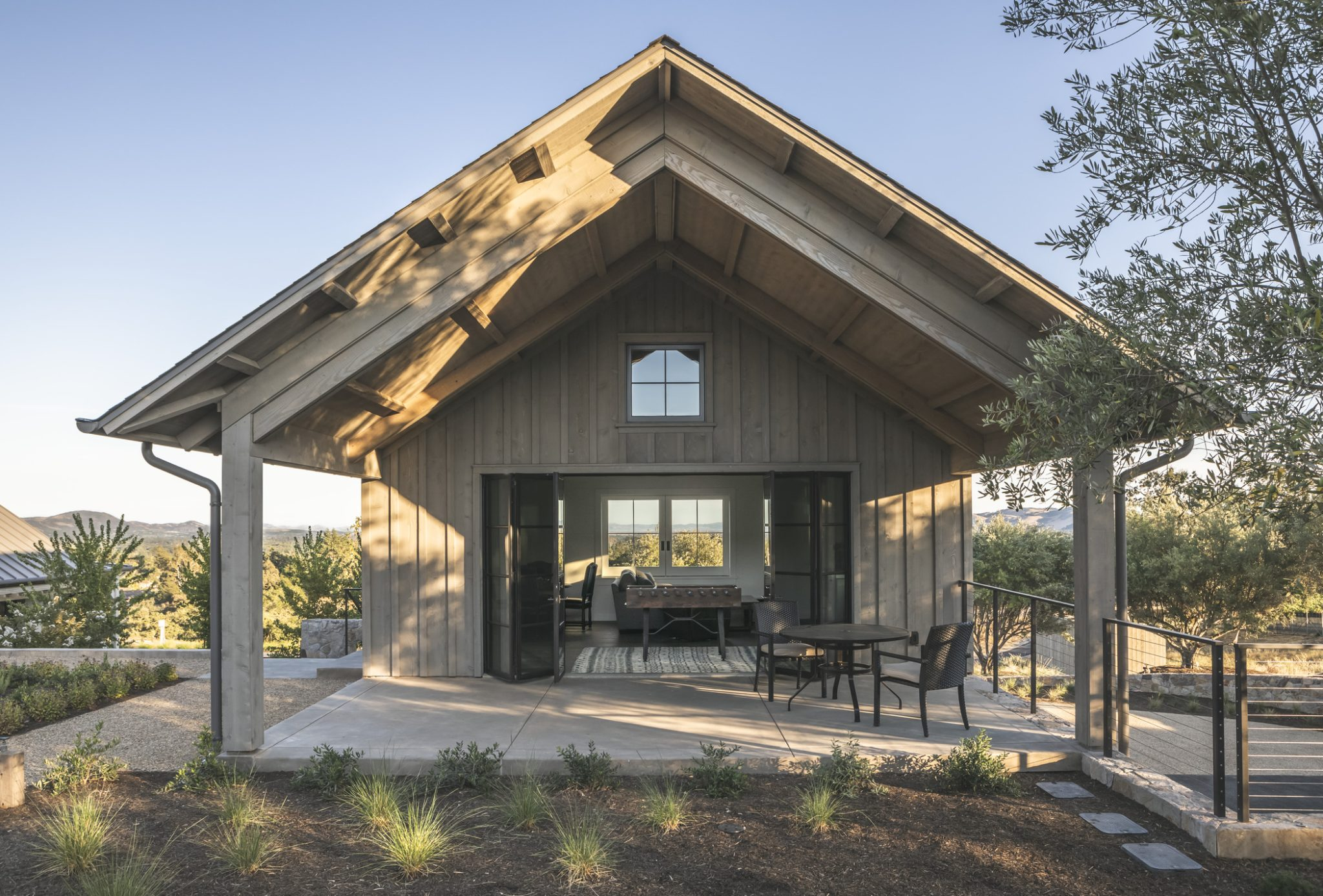 A small, A-frame garage serves as an added lounge space, and includes a pool table and seating area. Stained cedar siding gives the building a rustic appearance.
