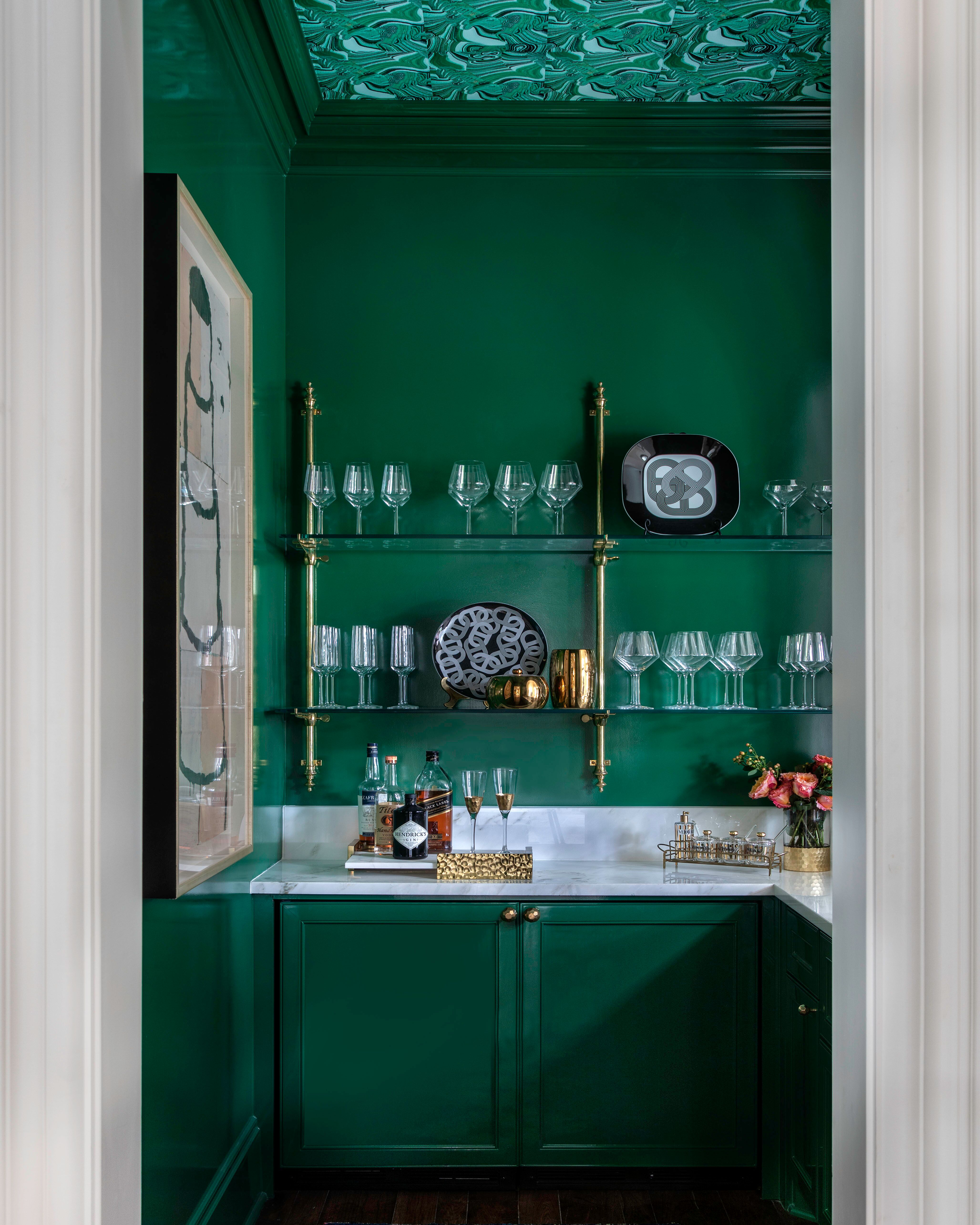 """Use Unexpected Accents. """"A dark, sexy color palette, brass or lacquered metal accents, an unexpected wallpaper, antique mirrors, and an interesting countertop all play into the way I begin the design,"""" says NicoleZarr.   The lacquered green walls, cabinets, and brass hardware in this space blend with the color scheme of the home, but also give the spaceits own personality."""