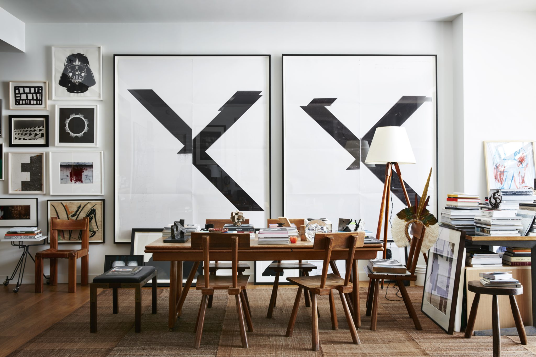 Two Wade Guyton prints preside over a Guillerme et Chambron table and Marolles chairs in the dining area of the designer's own SoHo apartment in a Gwathmey Siegel-designed building.