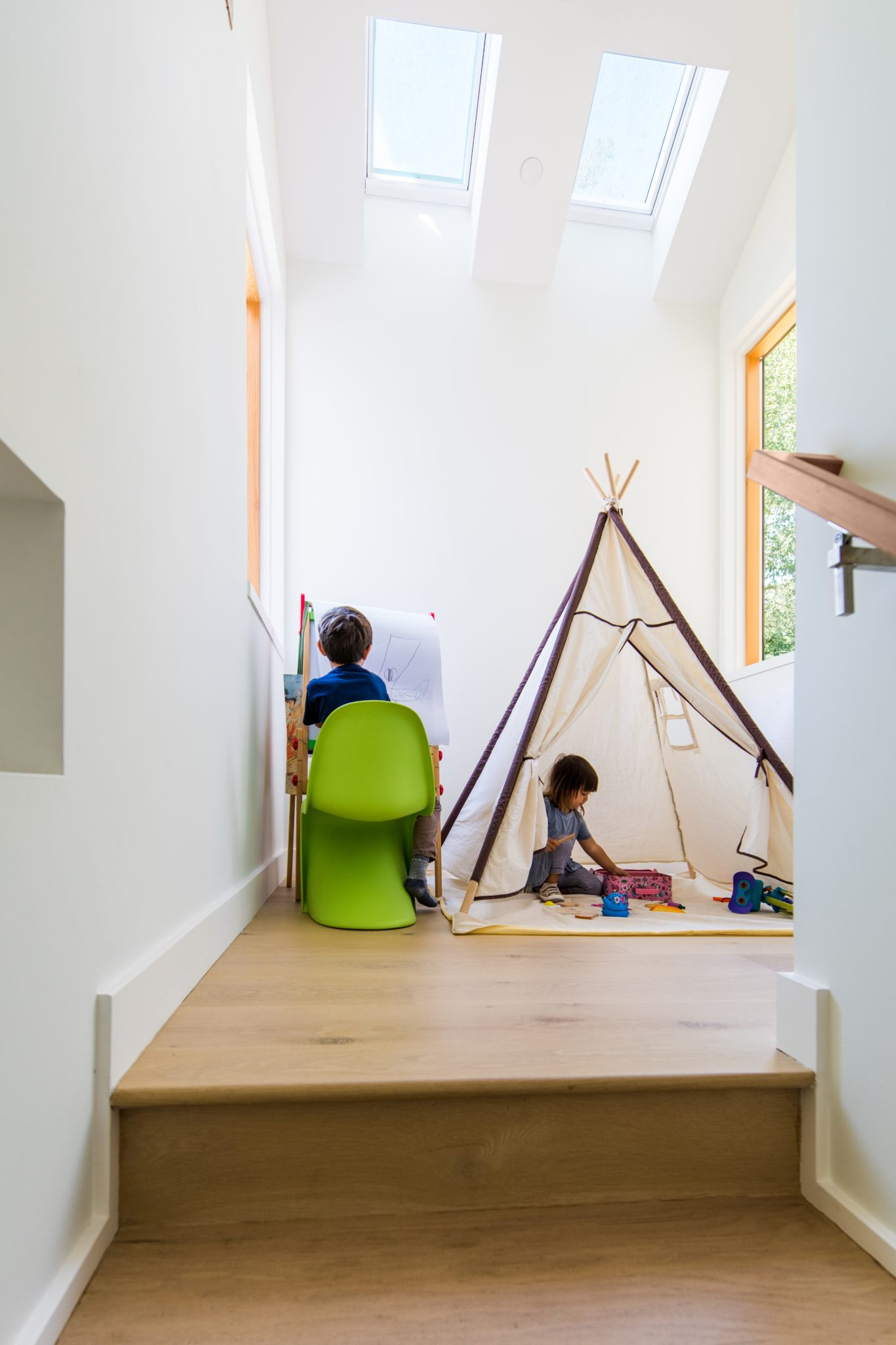 The extended stair landing is another example of a space that can naturally change as the family grows. Right now it can be used as a play space for the children, while in the future, it can be outfitted with a desk for the parents or used as a light-filled reading nook.