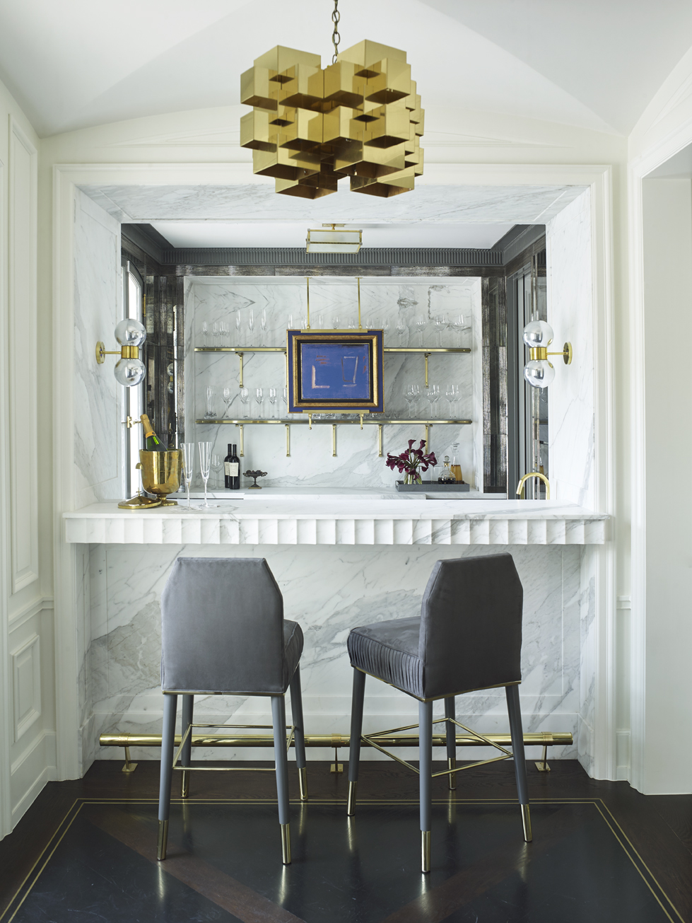 Because the clients enjoy entertaining, it was important for the design of the bar to aptly reflect the clients and their style. Palaciosdesigned a marble alcove for the bar and carved scalloping into the bar's edge. Antique mirrors and reededmercury glass flank the bar shelving.