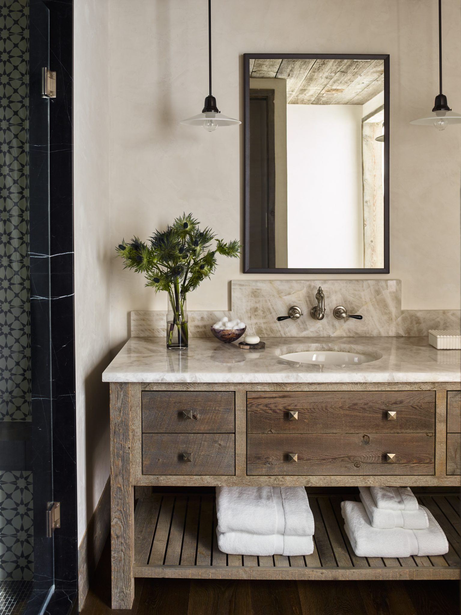 Simple and stylish, the guest bath has a custom vanity by Kylee Shintaffer. The Hudson Pendants from Urban Archaeology, metal-framed mirror, and chic countertop update the space.