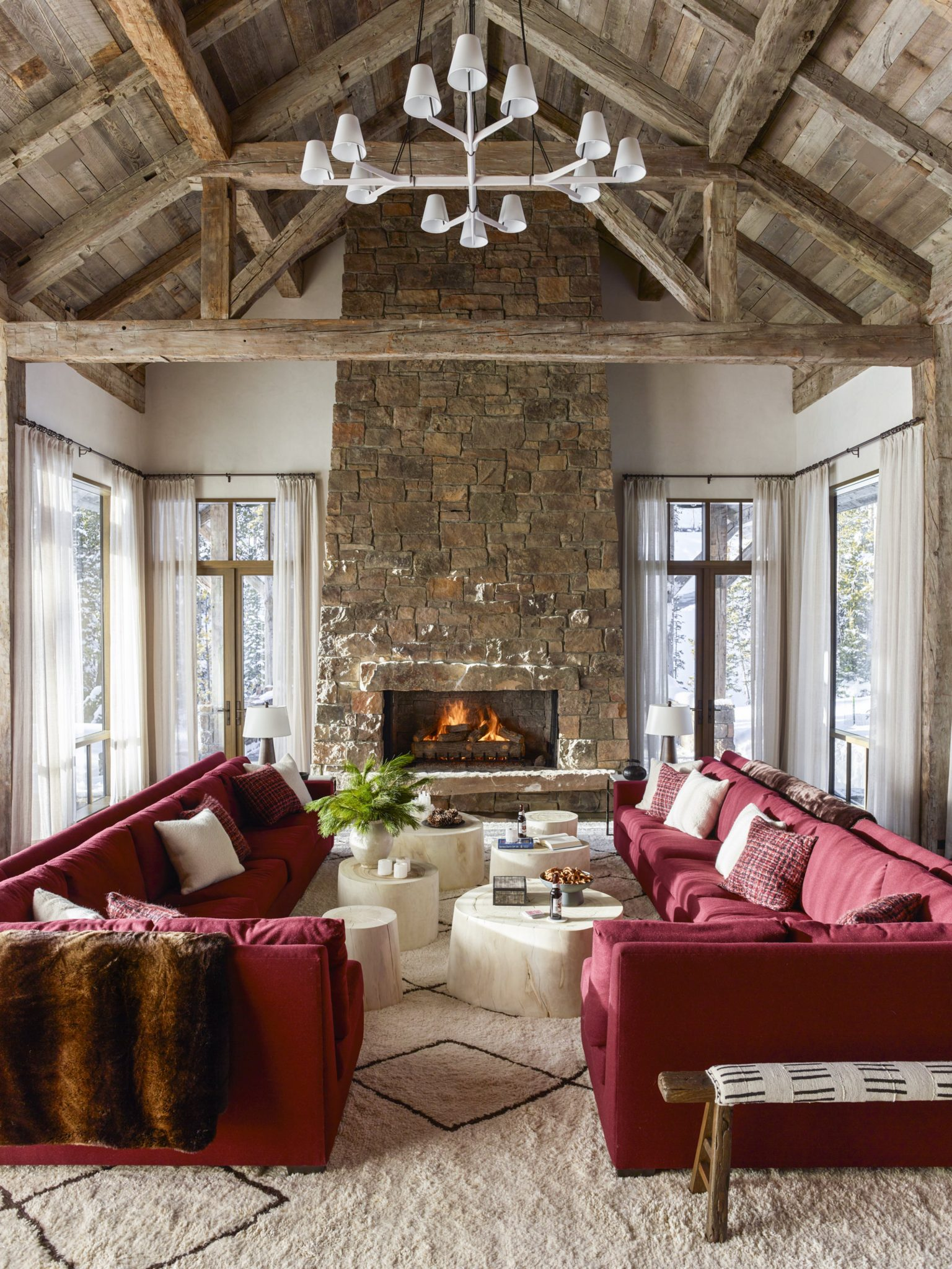 "Throughout the home, Shintaffer chose to include warm red tones — like the custom sectional covered in a Gastón y Daniela raspberry-colored wool in the living room. ""Deep berry tones were a great way to marry the wife's love of cool neutrals with the husband's interest in color,"" explains Shintaffer.  White and cream tones ground this space — like the Moroccan Rug from Jan Kath, the custom bleached pendant from Kalmar, and the bleached sycamore stump coffee tables by Sawkille Co. ""The bleached sycamore stumps allow for easy movement and flexible use and at the same time create a visual connection to the natural beauty beyond,"" notes Shintaffer."