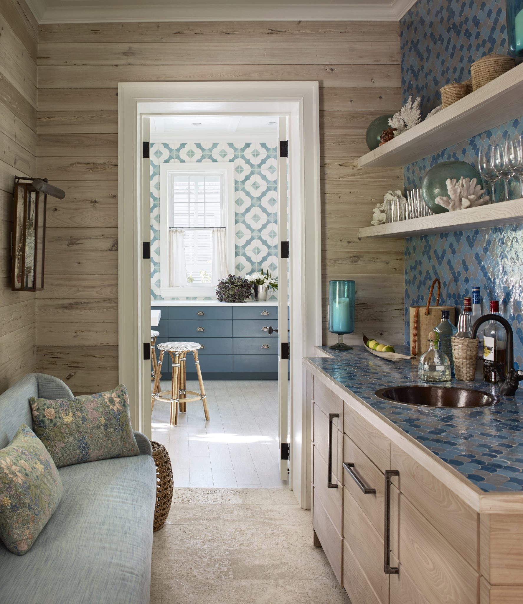 In a holiday house on Harbour Island in the Bahamas, the walls in the bar area are covered in pickled pecky cypress and colorful Moroccan tiles; the kitchen beyond is equally boldly patterned, with Cuban-style Katie tile from Villa Lagoon Tile.