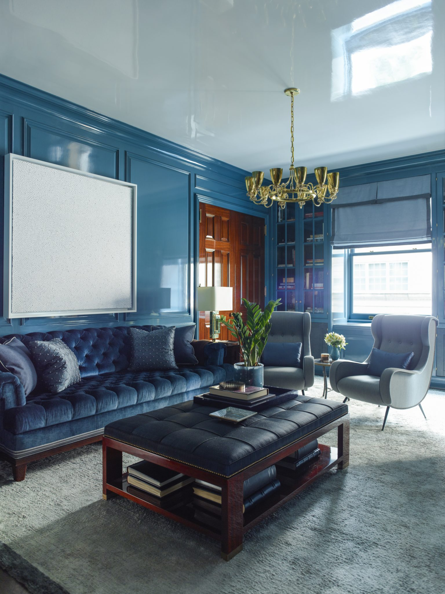 In aFifth Avenue duplex in a1912 buildingbyMcKim, Mead & White, Gambrel had thesitting room lacquered ahigh-gloss peacock-blue as a counterpoint to the adjacent waxed pine study;thevintage Italian club chairs areby Paolo Buffa.