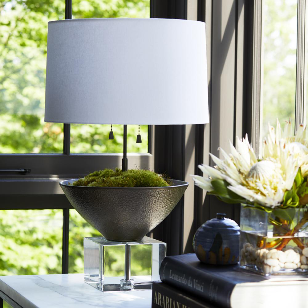 In this image, a vessel lamp is styled with moss. Since it's designed with a bowl, homeowners can use it as an opportunity to present a collection or add natural materials, as in this instance.