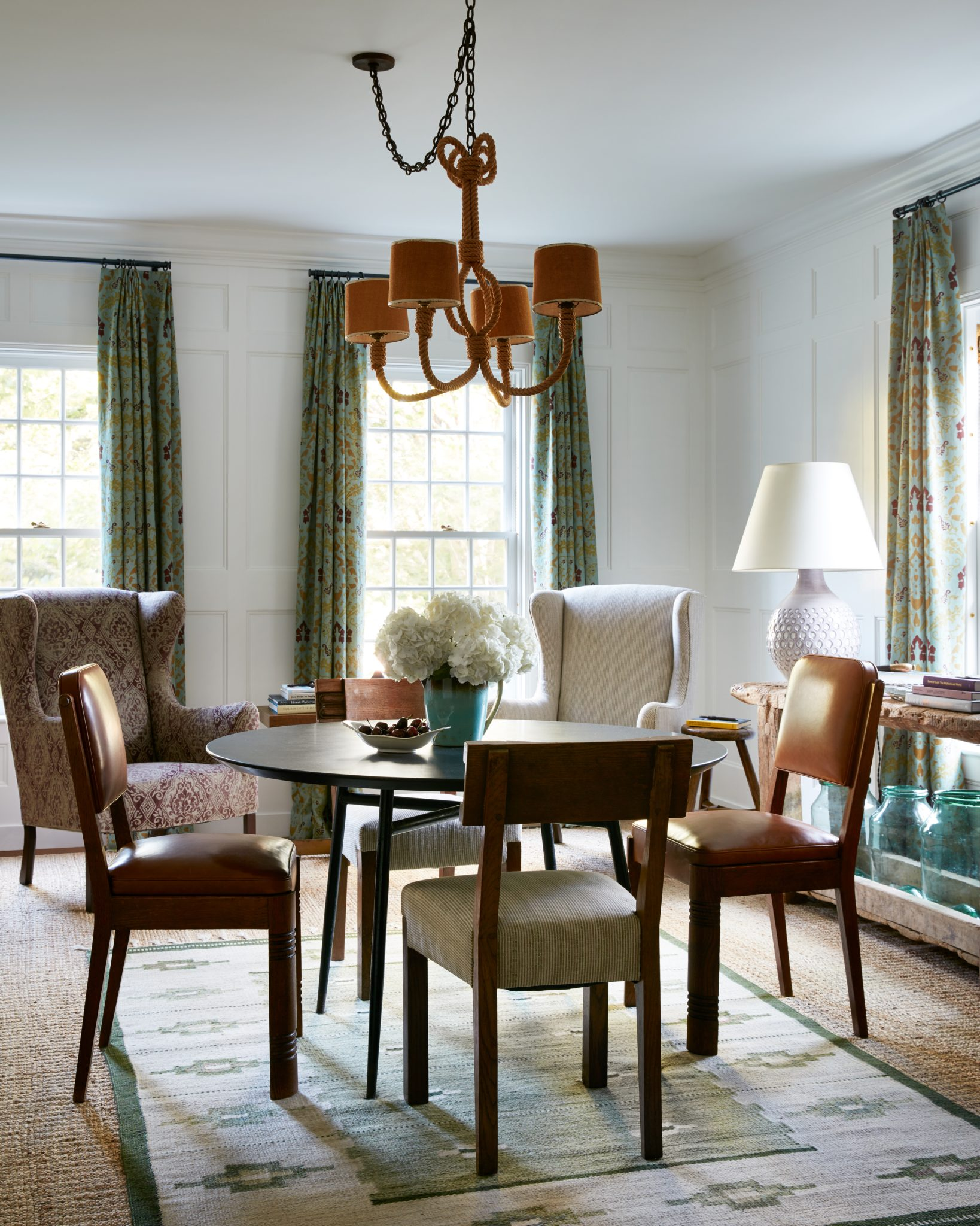 In a late-19th-century Hamptons farmhouse rebuilt by the designer working with Peter Pennoyer Architects, English and American antiques mix with midcentury designs of various nationalities, traditional fabrics, and eccentric items from far-flung locales. The dining room ensemble includes Charles Dudouyt chairs, an Audoux-Minet rope chandelier, and Børge Mogensen–style wingback chairs.