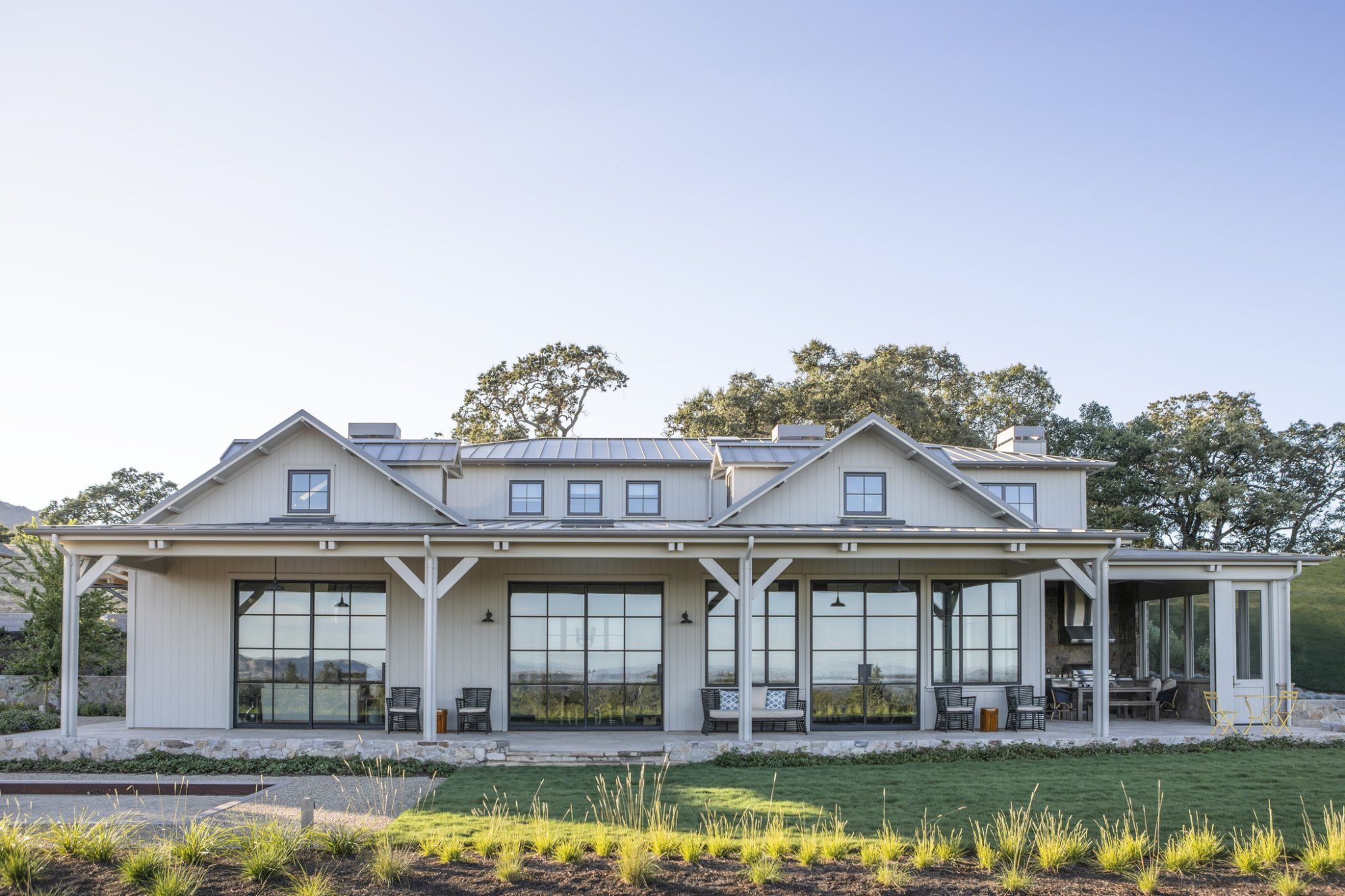 Although the clients and architects wanted wooden materials that would match the country aesthetic of the property, they opted for painted cement board from Boral that would resemble wood sidingand protect against wildfires. Nickel-gap detailing helps the siding to stand out, and the shadowed spaces between the boards run parallel to the tall, gridded glass doors, which offer an unconventional, contemporary take on traditional farmhouse styles. At the base of the home and surrounding buildings, full-dimension stone was used to integrate the exterior with the retaining walls.