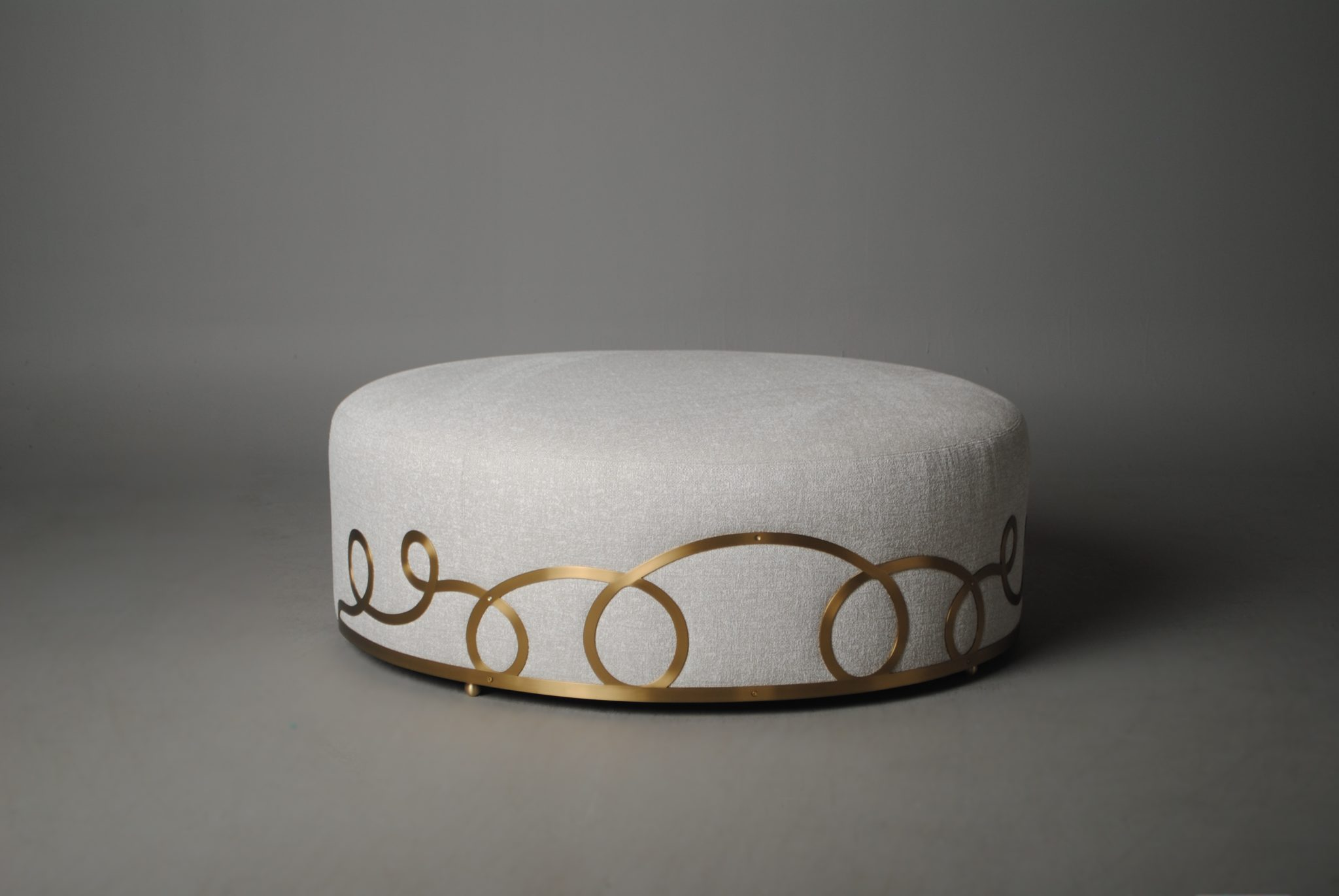 Known for his boldness and metallic touches, Larry Laslo is launching several pieces with Chaddock including the Loop de Loop Ottoman, a 50-inch upholstered round ottoman with a whimsical flat brass loop design.