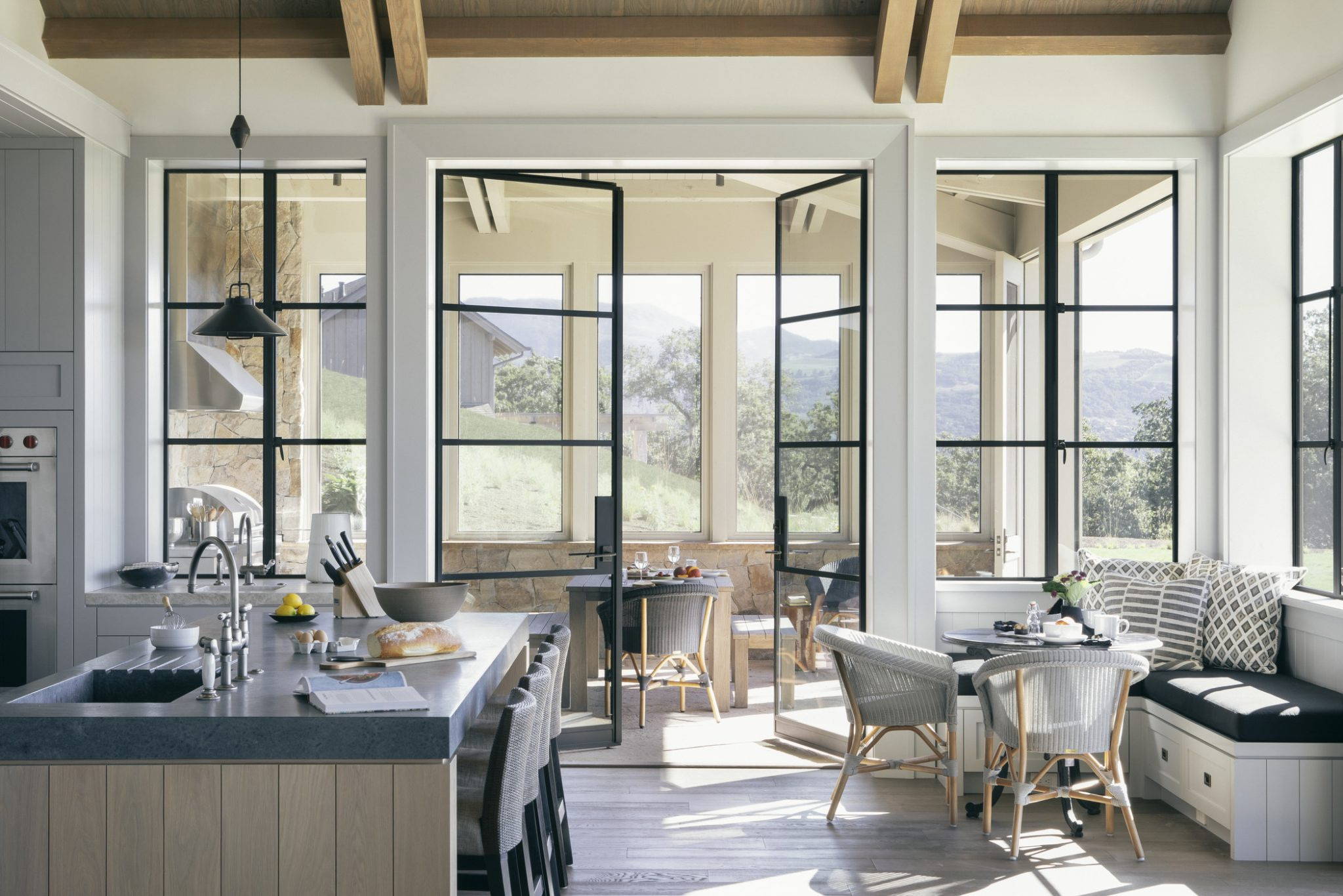 Indoors, the layout is fairly open, with a central axis that runs through the center of the home and extends outward on both ends. High, beamed ceilings enhance the large scale of the space.