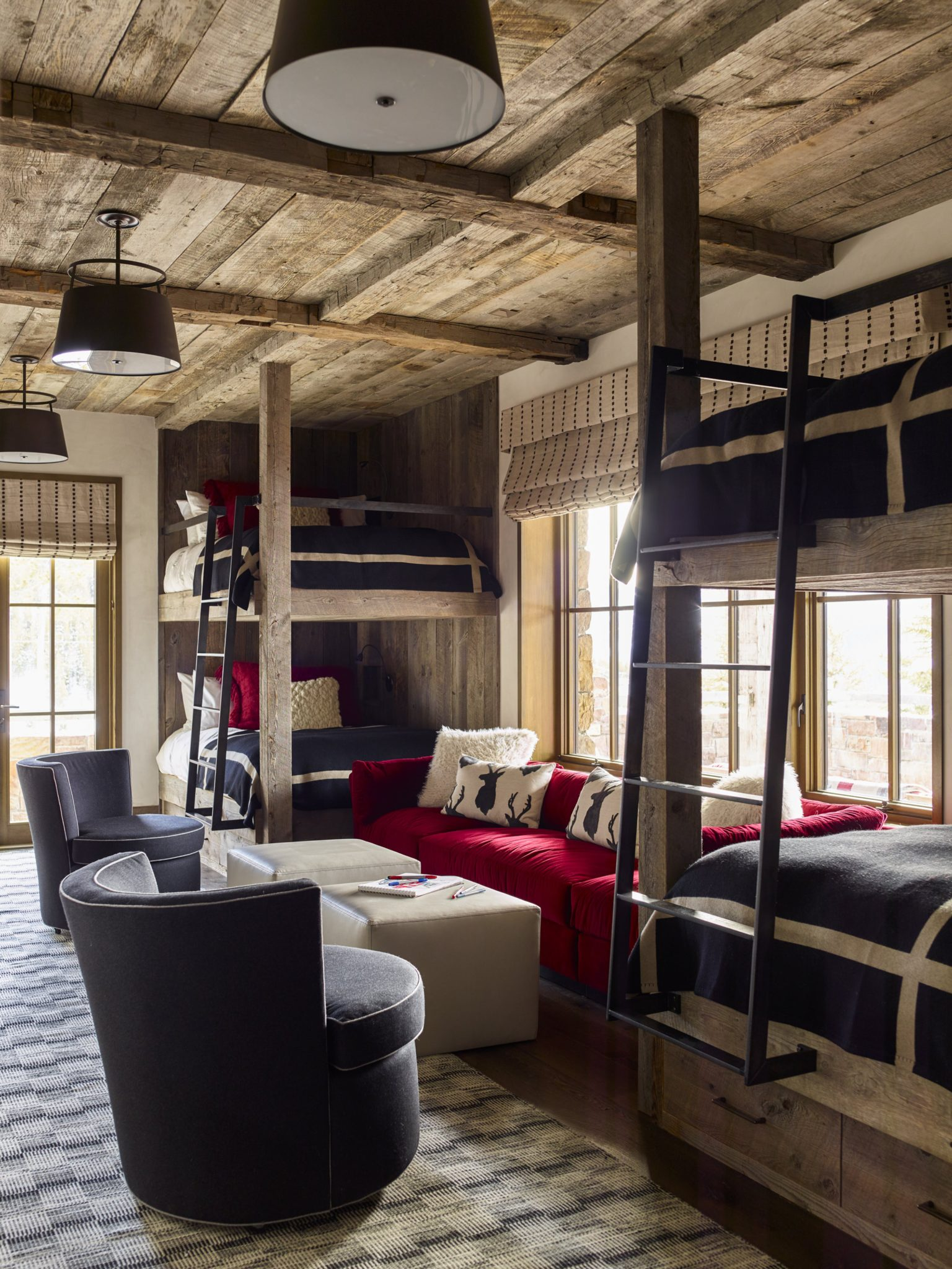 Ideal for children or teens, this rustic bunk room is full of plush seating — like the Harvey Probber-inspired sofa covered in Dedar mohair, vintage swivel chairs upholstered in Casamance wool, and custom ottomans covered in Kravet leather. The bunk beds were made custom by Shintaffer and the pendants are from The Urban Electric Co.