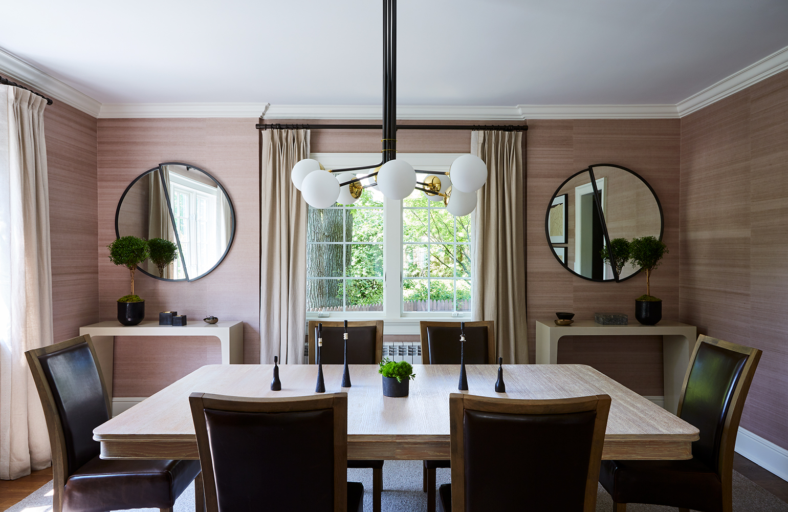 A blush-colored wallcovering from Kneedler|Fauchère helps create a warm, beautiful atmosphere in the dining room. Custom mirrors bring geometric shapes to the space, as does the orb lighting fixture from Bourgeis Boheme. Rogers & Goffigon fabric frames the views through the window.