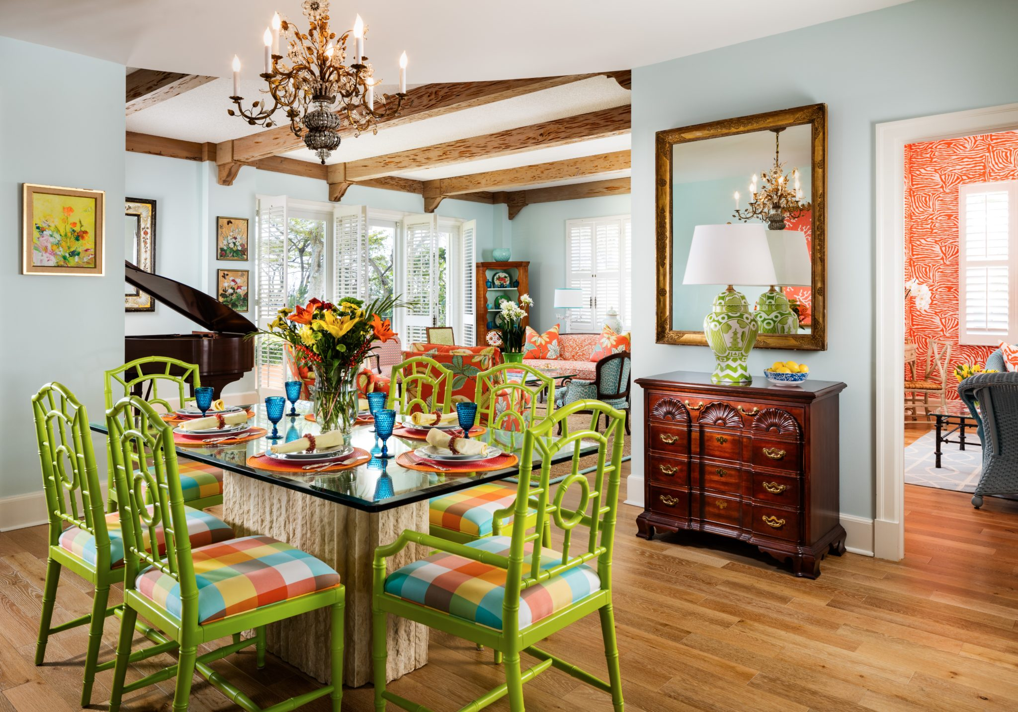 An antique chandelier hangs above a vibrant dining area. by Gil Walsh Interiors