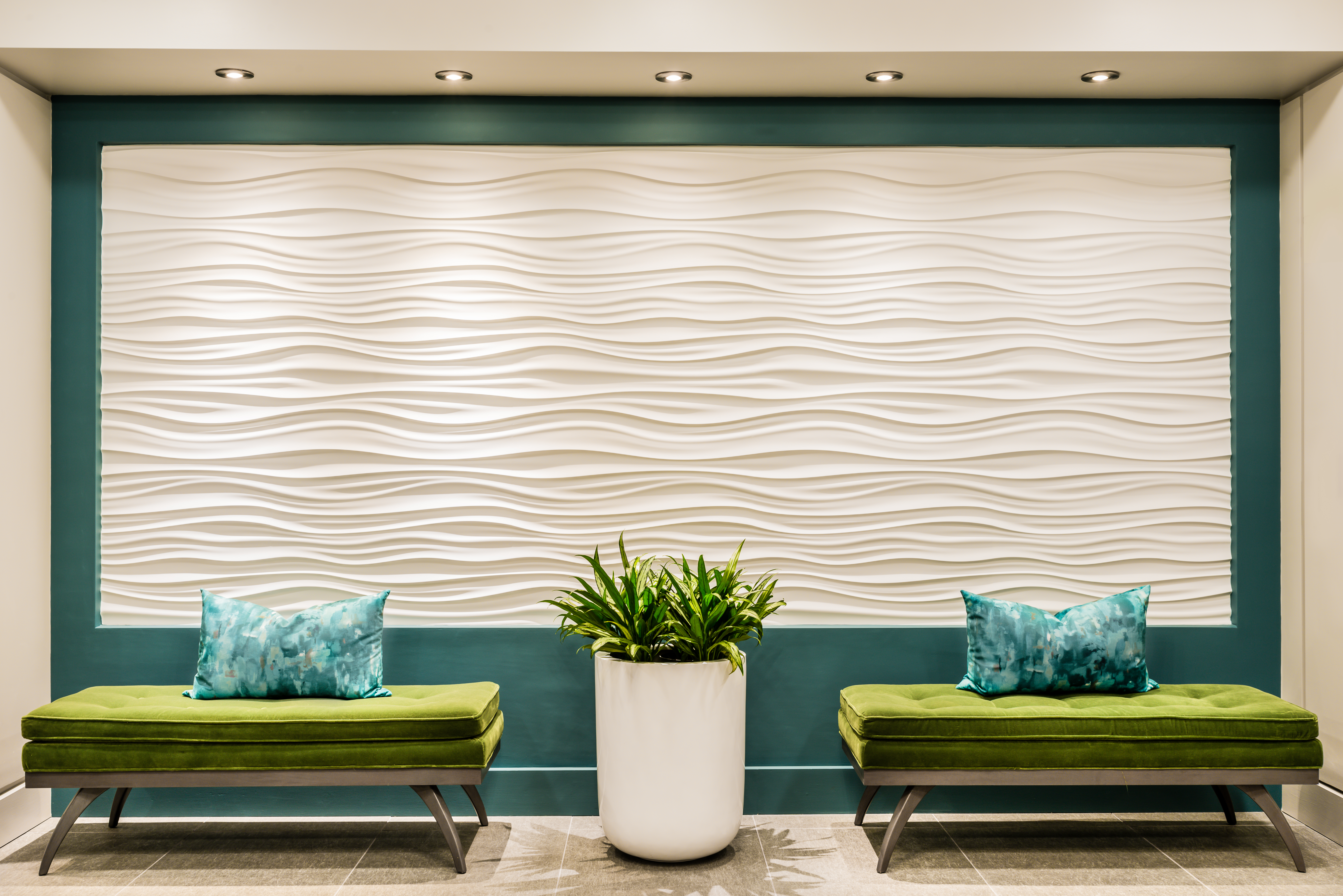 """7. 3D and Textured Wallcoverings   Texture is essential in any well-designed space. """"Dimensional wallcoverings are unexpected and unique, and add interest to a space without the need to add color,""""says Jill Najnigier ofJN Interior Spaces. """"Previously this wall was an opening to the building's mailroom, an unwanted focal point in the lobby. We relocated the entrance to the mailroom, allowing for the creation of a feature wall. My goal was to create a sculptural feature wall, a dynamic focal point. The 3D wave pattern was perfect, a nod to the Boston harbor just outside the door."""""""
