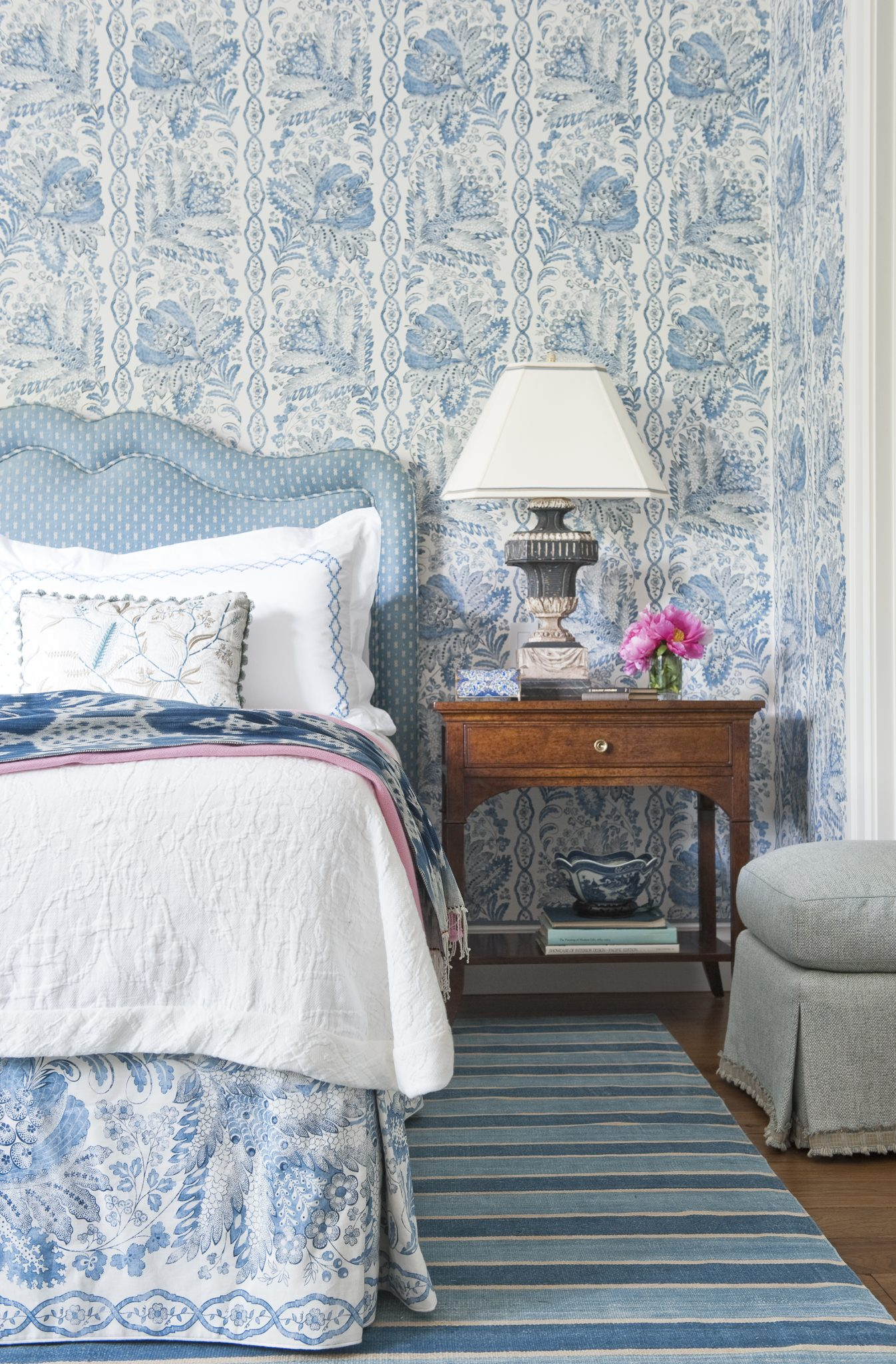 In the guest bedroom, the headboard was custom-designed byTucker & Marks and upholstered in fabric from Clarence House. The wallcovering is a printed linen from Suzanne Tucker Home, and the coverlet is also from Suzanne Tucker Home. The bedside tables are from Charles Fradin.