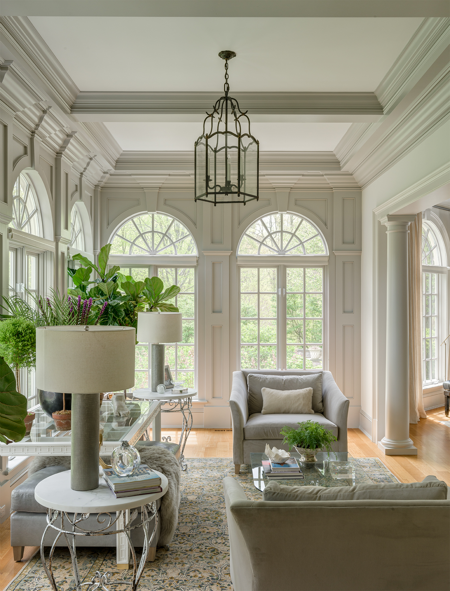 An inviting sunroom mixes plants with plush upholstery in tonal grays. by Shelley Morris Interiors