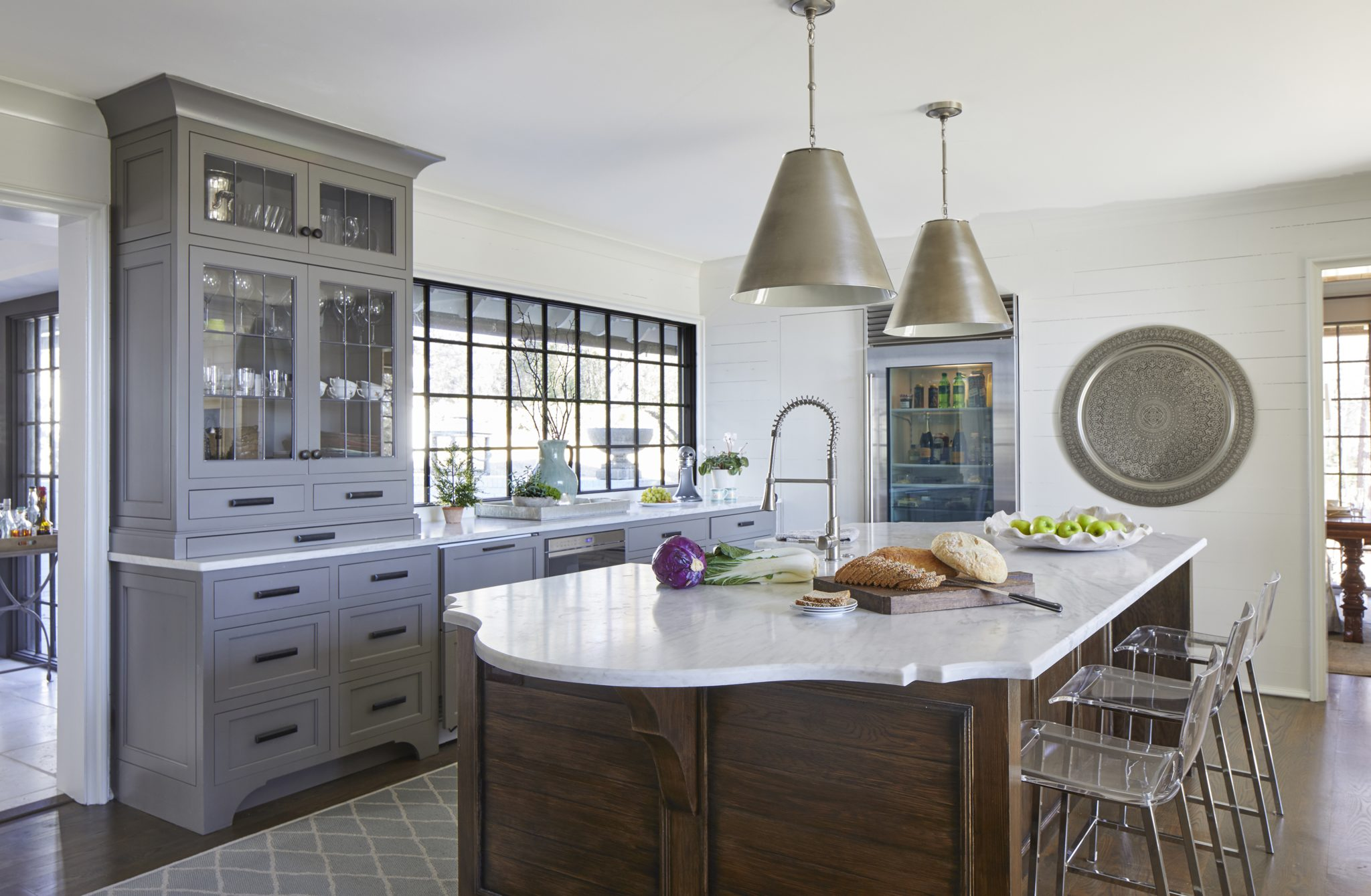 The kitchen design showcases a pared-down aesthetic that still has personality. Custom cabinets from Heath Hughes, Inc, stone countertops from Pacific Shore Stones, and Ashley Norton hardware from Brandino Brass set the tone; the metal pendant lights are by Visual Comfort.The Sub-Zero refrigerator and Wolfappliances offer functionality as well as beauty, while a hidden pantry brings additional storage and an unexpected element to the space.