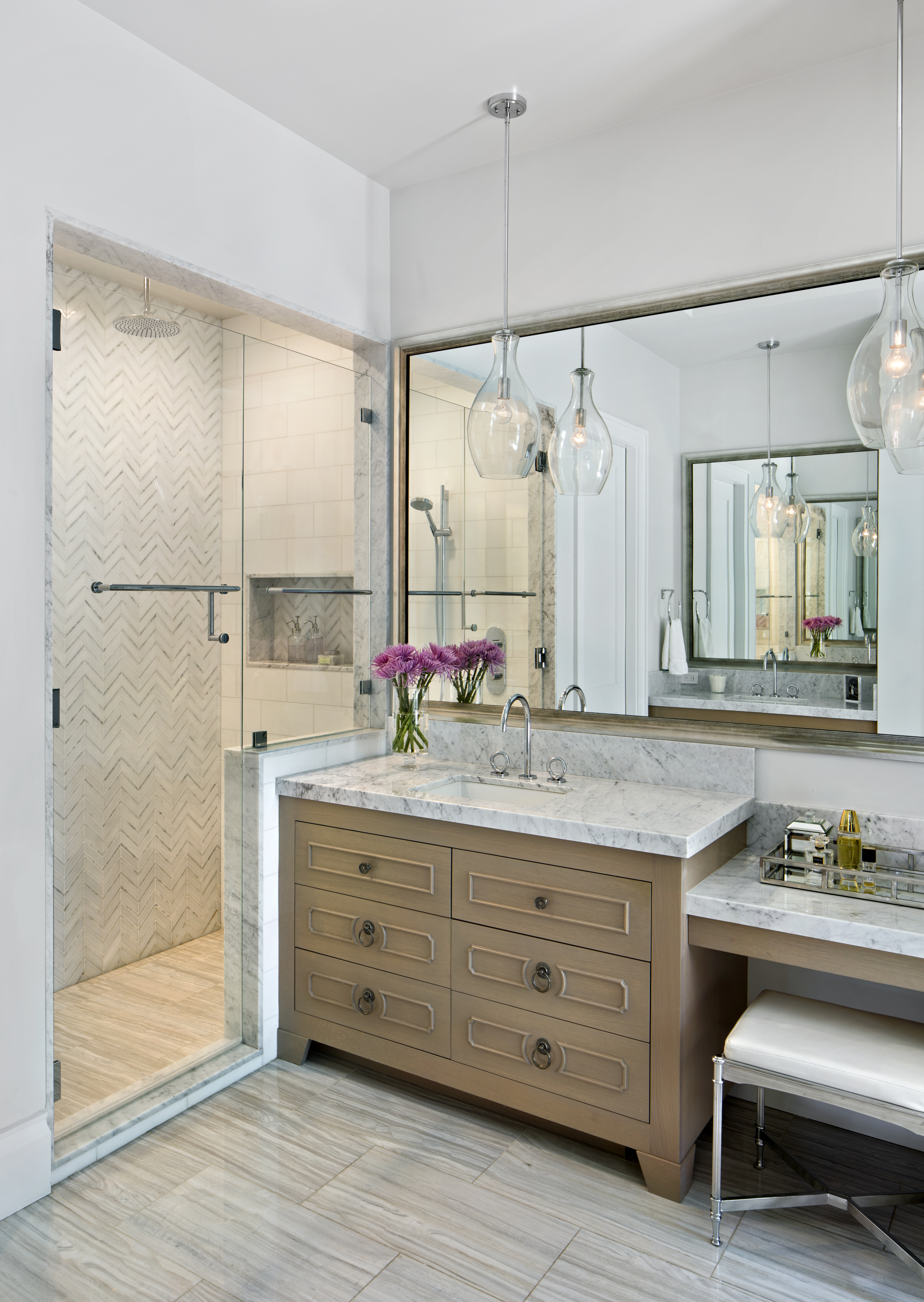 The master bath features Thassoswall tiles from New Ravenna and Siberian Sunset floor tiles from Walker Zanger. A slab of Carrara marble is used to create the modern countertops. Silver hardware, two glass pendants, and a large wall mirrorcomplete the design of the space.