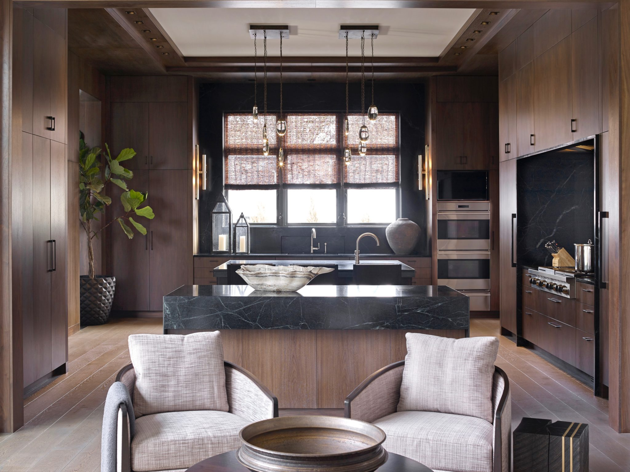 A stylish kitchen mixing dark woods and marble by Joel Kelly Design