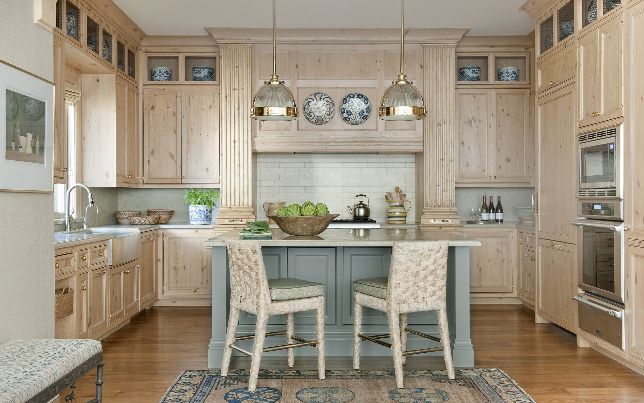 Pine cabinets and limestone counters create a natural, contemporary look in the kitchen. The holophane ceiling pendant light fixtures are from Ann Morris Inc., and the counter stools weresourced fromthe Wicker Works. Antiques, however, are still present: the English mochaware country jugs are from around 1880, as is the wooden dough bowl.