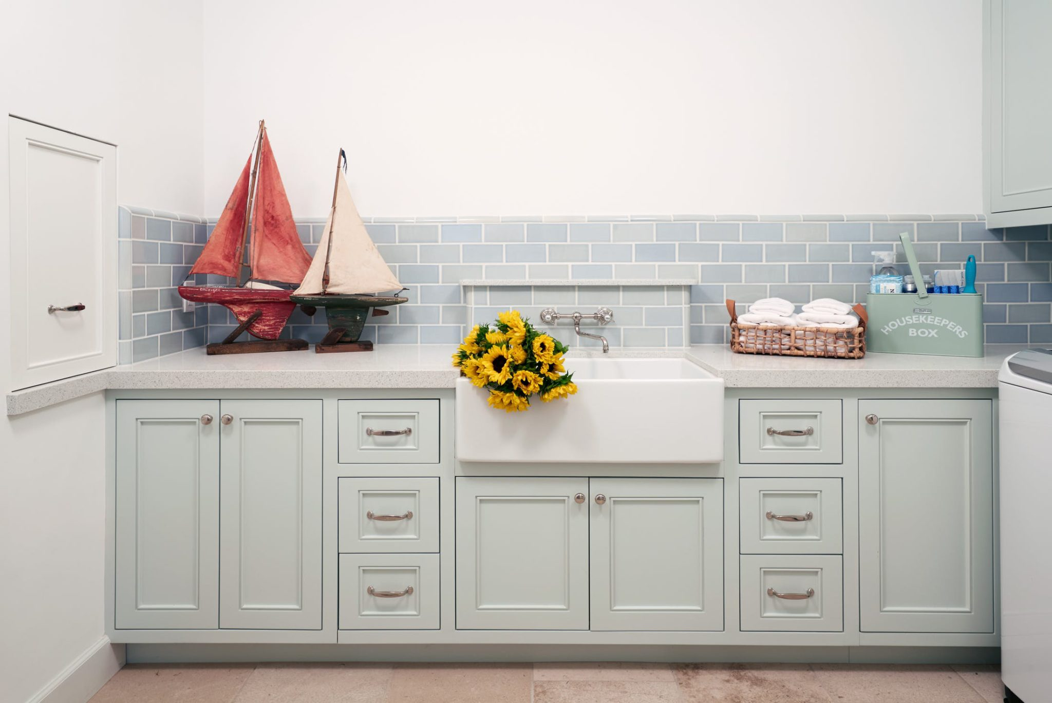 A farmhouse sink by Waterworks in a charming laundry room designed by Erin King Interiors.