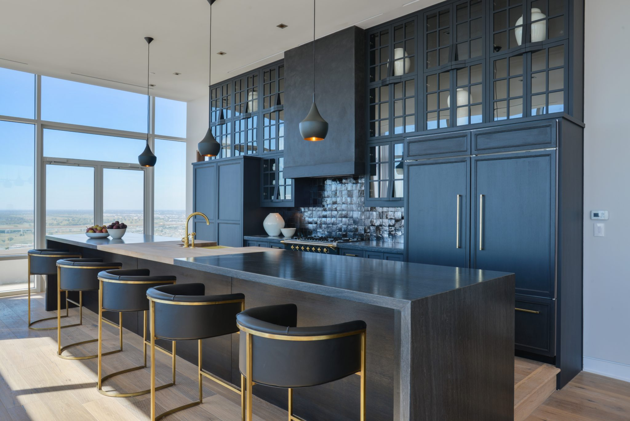 A chic penthouse kitchen in black and gold by Ohara Davies-Gaetano