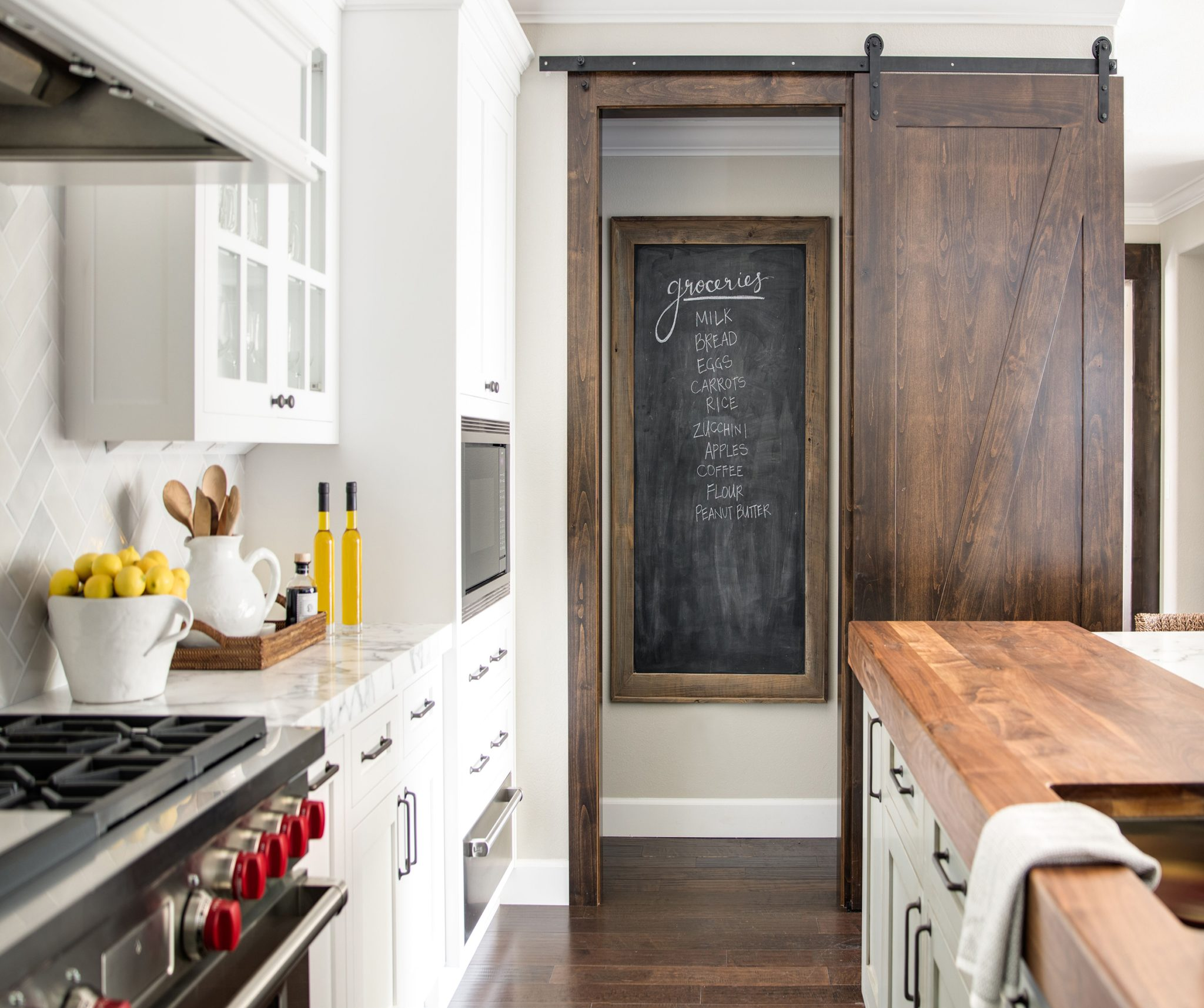 A barn-style pantry door in the kitchen and clever framed chalkboard for lists. by Kriste Michelini Interiors
