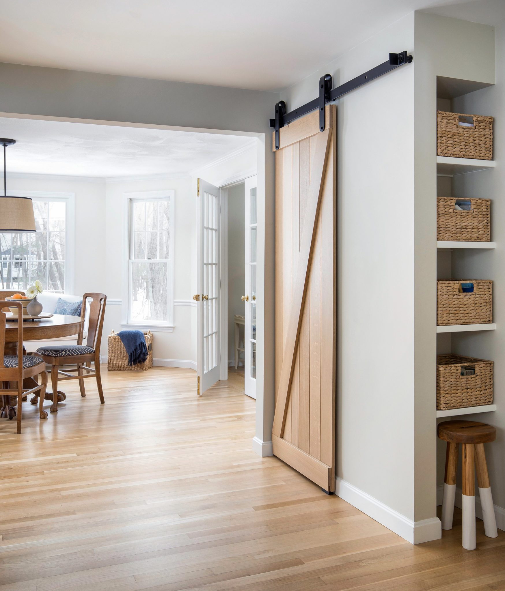 Natural oak barn door kitchen pantry with bronze hardware and breakfast room. by Sophia Shibles Interiors (formerly SCS Design)