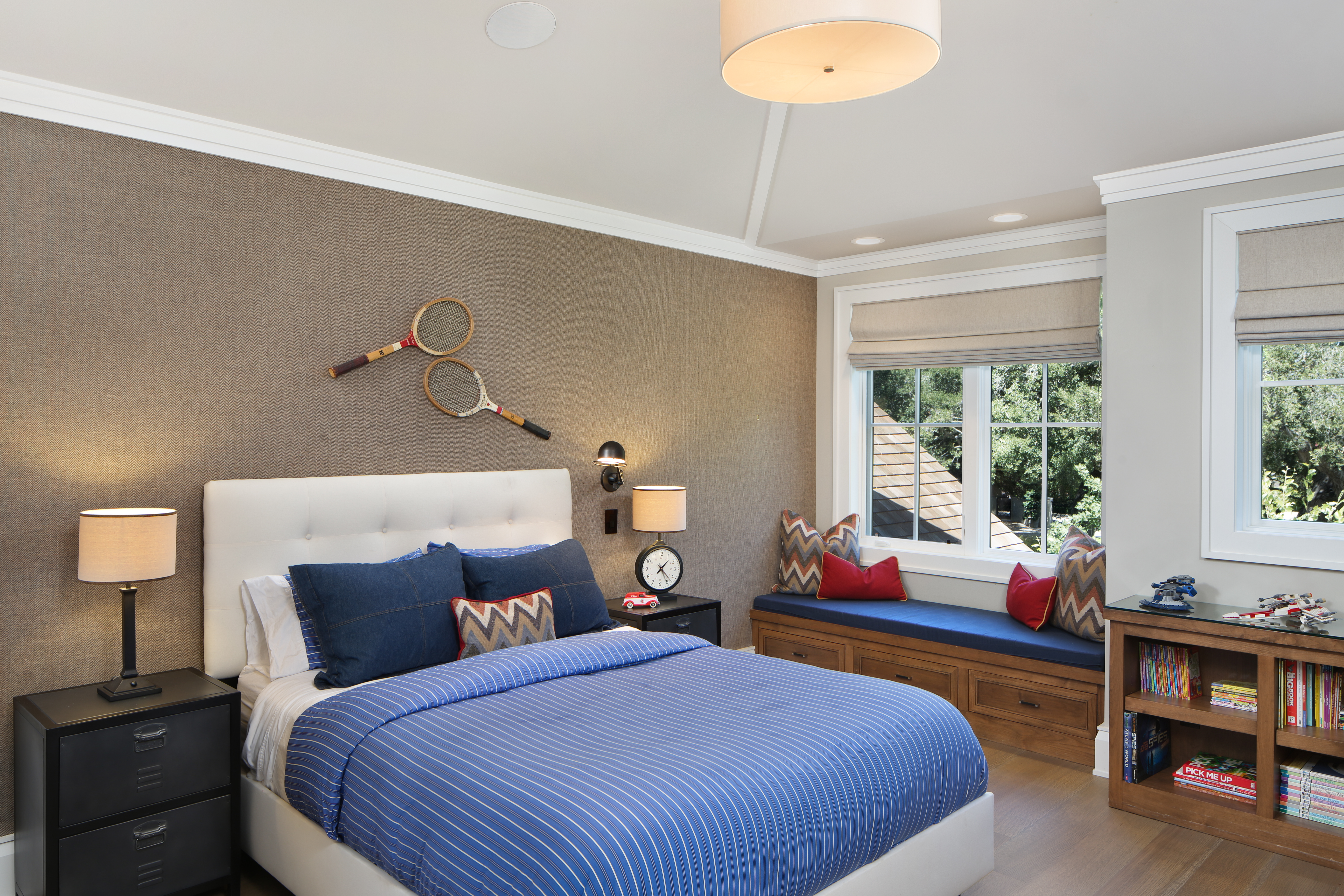 The boy's bedroom blends a youthful feel with sophisticated design. Serving as an accent wall, a chic mosaic is made up of pebbles from Island Stone. Tennis racks are used as decor above the bed, adding a playful touch to the space. Toys are displayed around the room, from the nightstand to the bookcase. To contrast the playful tones of blue and red, the team at Sullivan Design Studio uses wood-like tiles from Ann Sacks and two dark wood nightstands.
