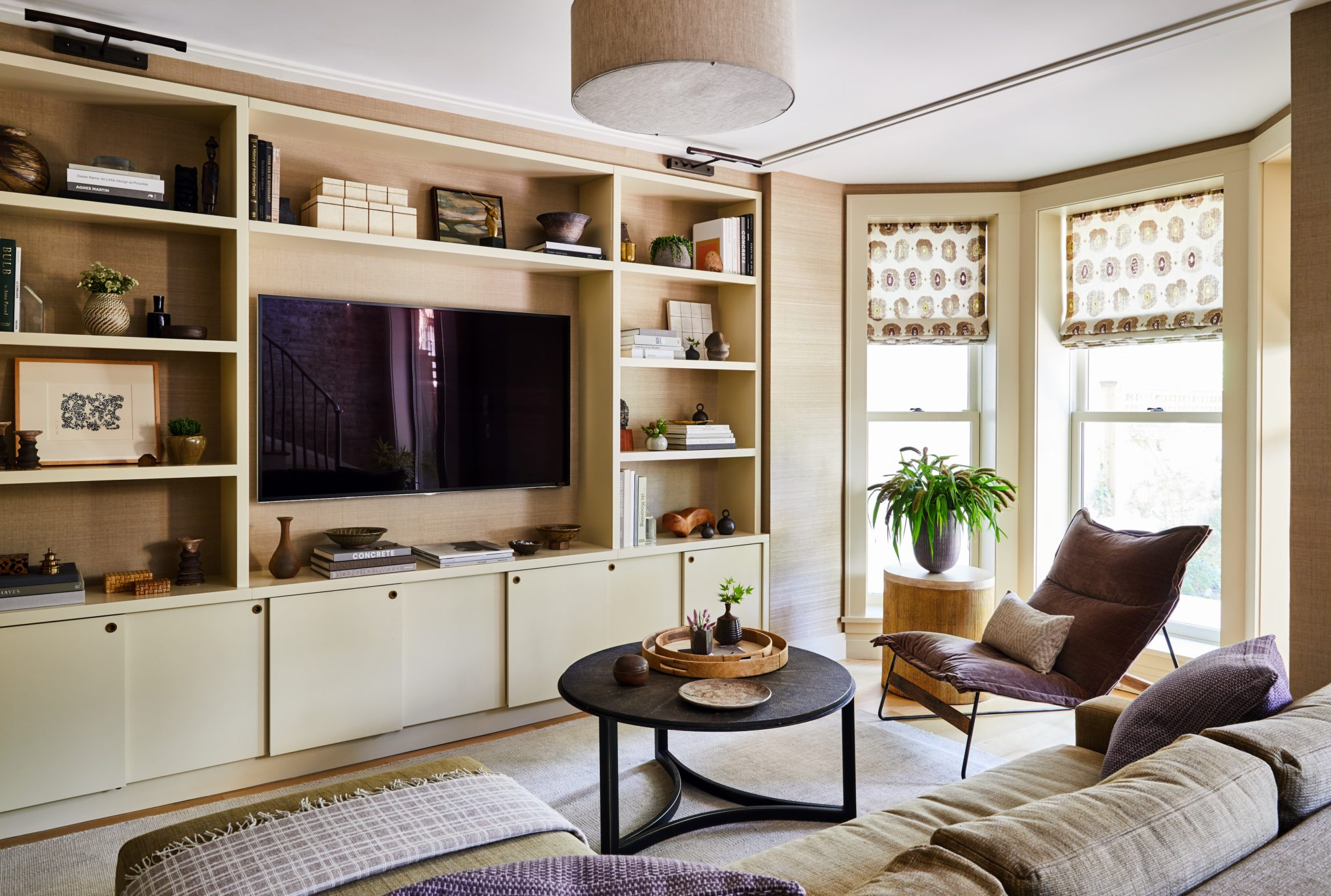 A grasscloth wallcovering from Sonia's Place in a natural hue covers the walls and is visible through the built-in media cabinet, custom created by NR Wood Design. Enger selected Claremont fabric for the window shades, Holly Hunt fabric for the custom sectional, and Claremont velvet for the Environment lounge chair. A custom wool flat weave runs underneath the furnishings, matching the color of the custom linen drum shade. The bookcase lighting is from A. Rudin; the occasional table is from Gabby, and the faux shagreen coffee table is from Dwell.