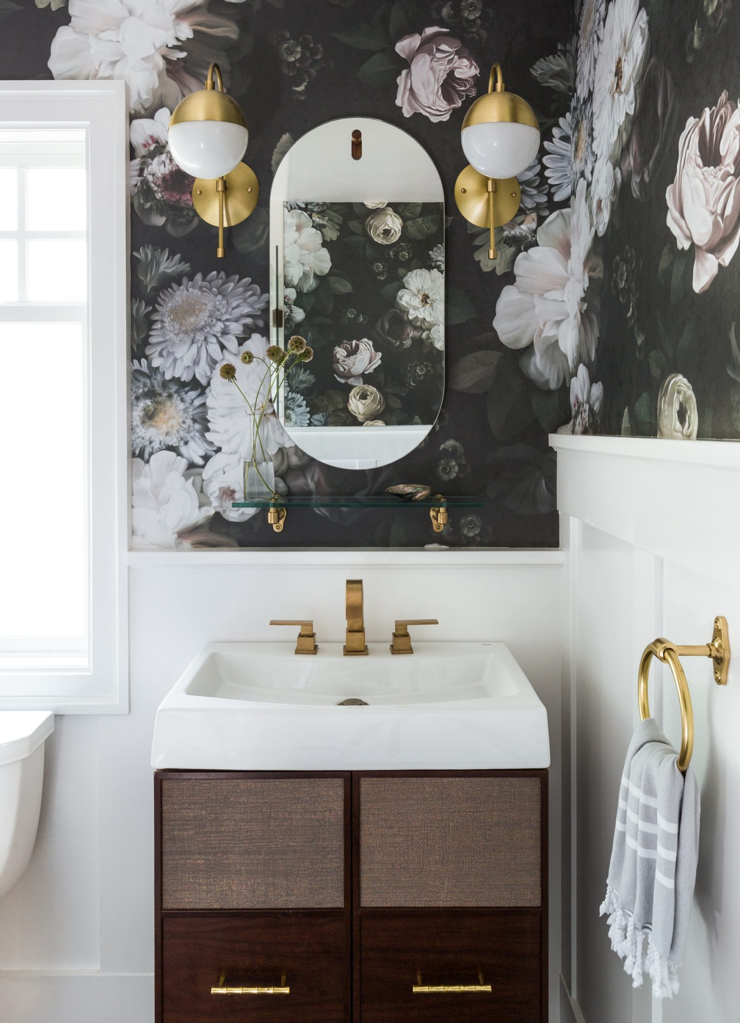 In the powder room, a dark floral wallpaper featuring painterly blooms is from Ellie Cashman Design. The custom vanity was built by J Wanamaker Cabinetry, and the mirror is from Blu Dot.