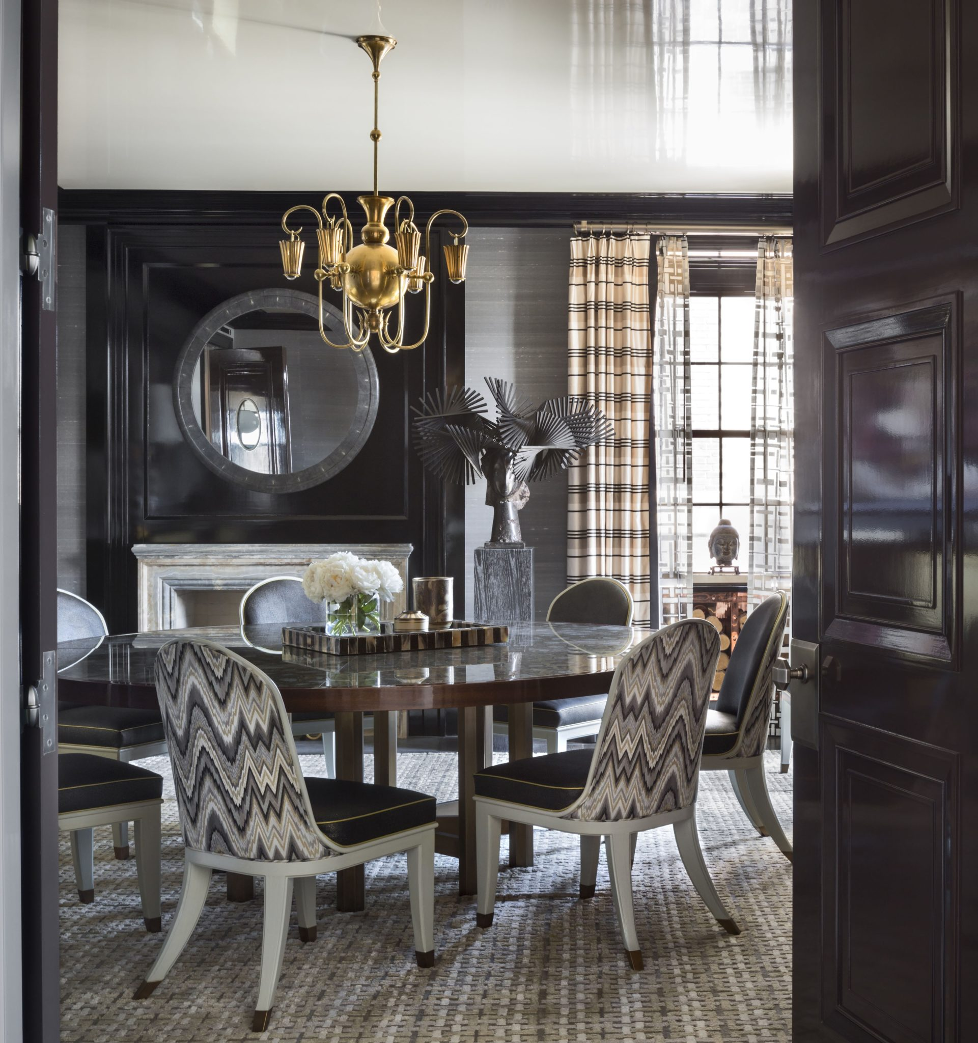 The dining room window was repositioned to favor the view and to accommodate a new fireplace. The dining chairs and the églomisé table are custom designs. The circa-1925 chandelier is from H.M. Luther, and the rug is by Beauvais Carpets.