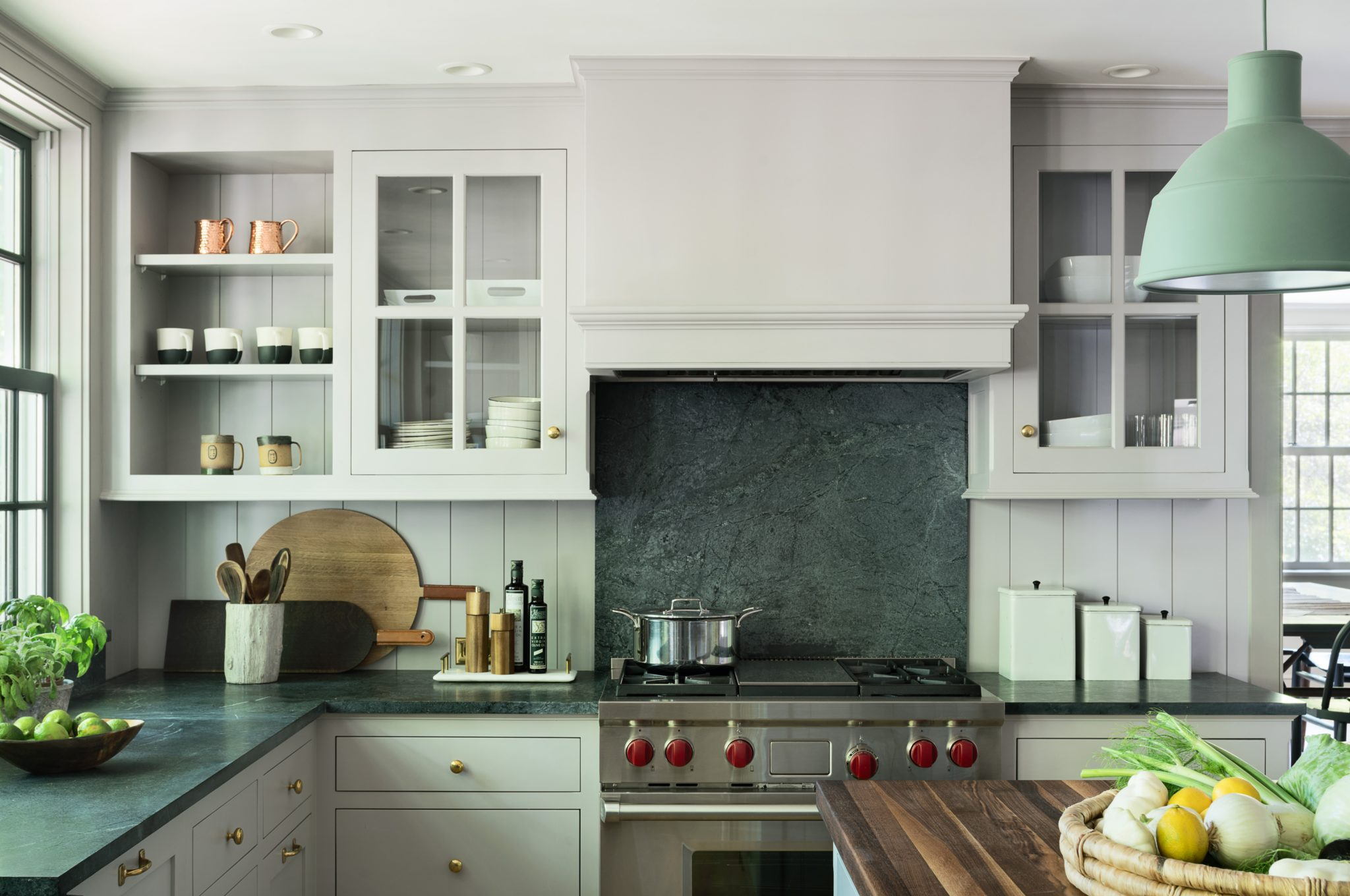 The kitchen counters and backsplash are stone, the range is by Wolf, and the pendant light is by Muuto.