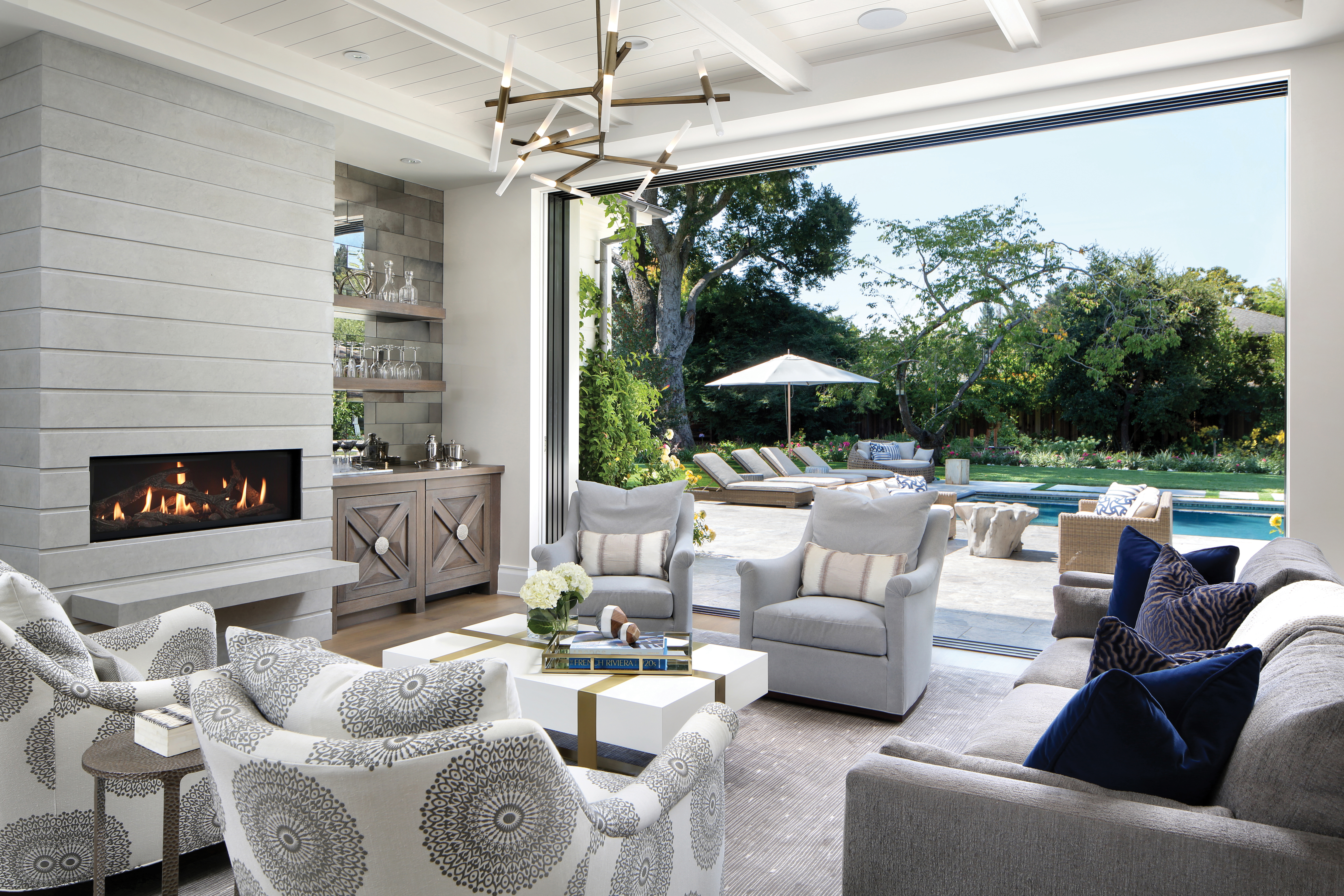 Overlooking the green backyard, the charming living space boasts aneutral color palette that blends seamlessly with nature —like the white wood paneling,light oak cabinetry, and limestone fireplace. The white coffee table is from Plantation Design and a gray sofa from Lee Industries is upholstered in Kravet fabric. Chairs from Hickory Chair are completed with Robert Allen fabric. Throw pillows from Osborne & Little, Kravet, and Larsen add extra texture and a touch of color to the inviting space.