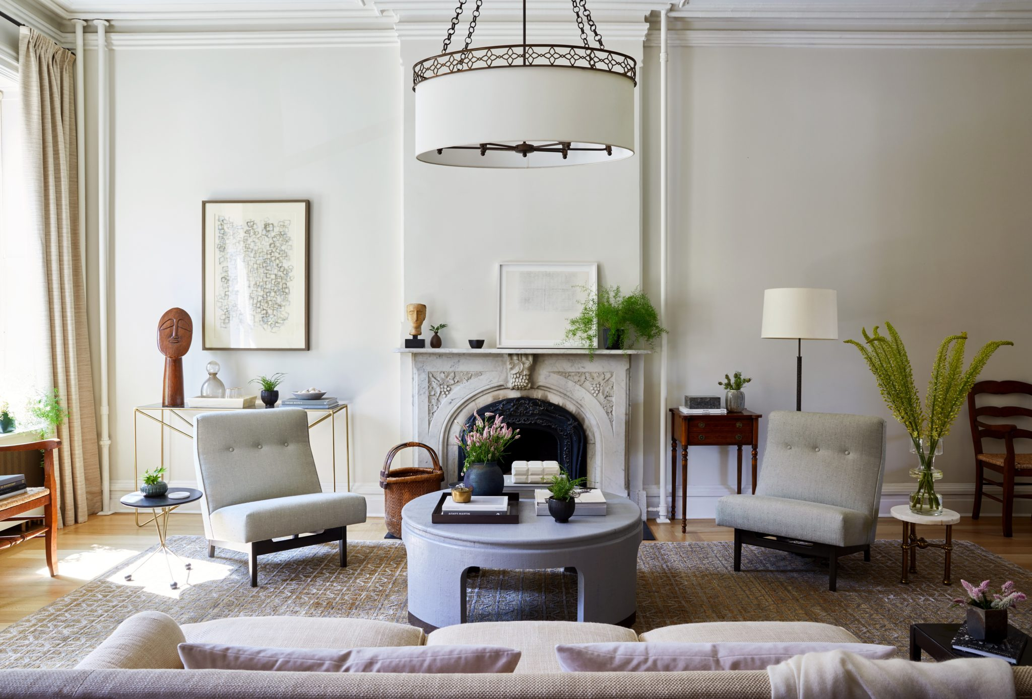 An engraved fireplace references the home's 100-year history. The circular coffee table in the center of the room was a choice find from Chairish; the textured table upholstered in linen was originally crafted in the style of 20th-century German product designer Karl Springer. On either side of the fireplace, vintage chairs by Jens Risom, the Danish master of Midcentury modern design, are upholstered in Toile Chenonceau fabric from Claremont. Draperies designed with Holly Hunt silk let in light from the large windows. Artworkby Heidi Kurko and Jean Wolf enhancethe beauty of the space, and the sofa and antique side table are the clients' own.