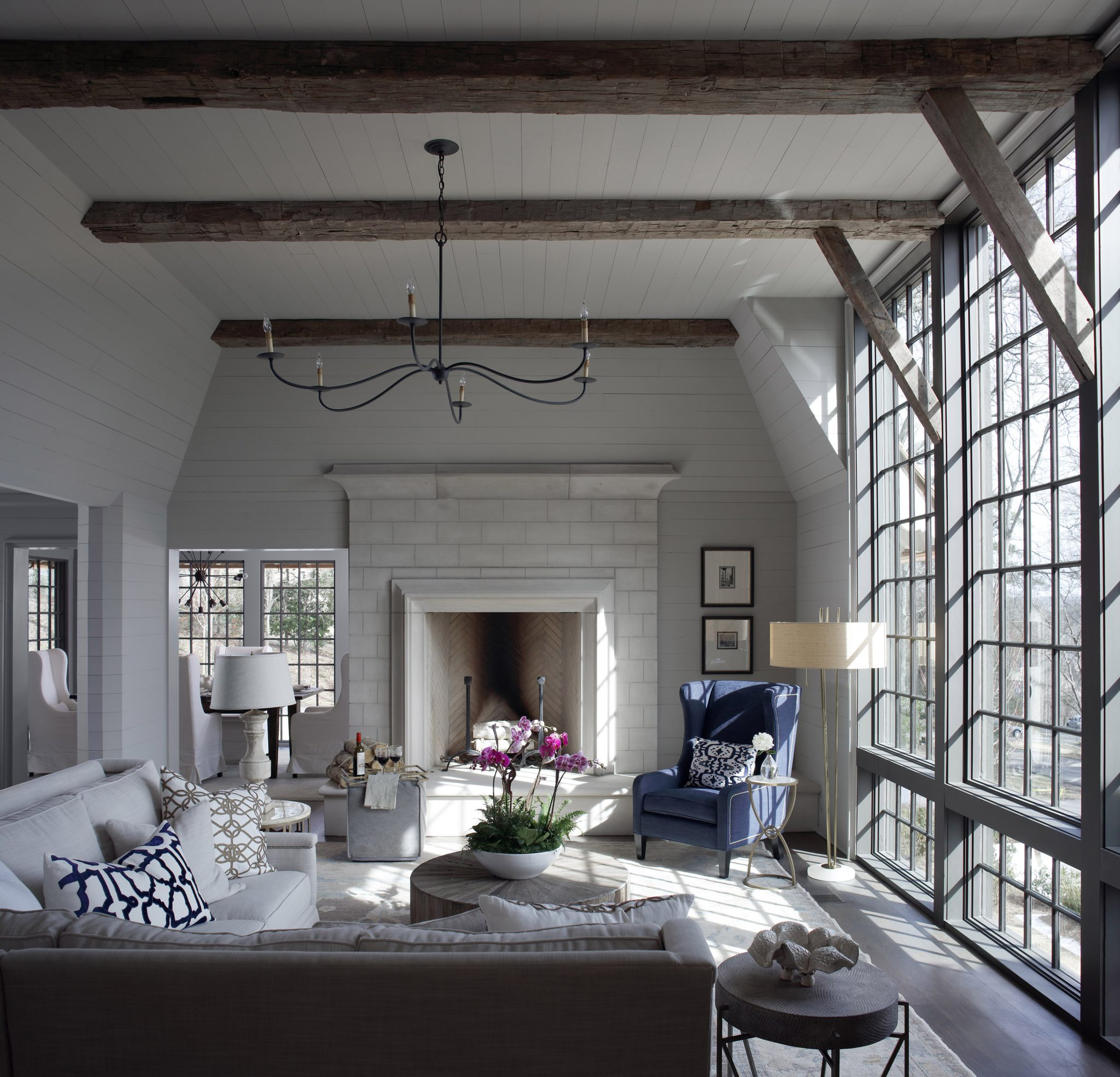 A sleek, long-armed chandelier from Currey & Company ushers delicacyinto the design of the great room. The sofas, coffe table, and armchair are from Gabby. Underneath, a rug fromKing's House Oriental Rugs in mixed neutrals offers a creative foundational layerfor the furnishings.
