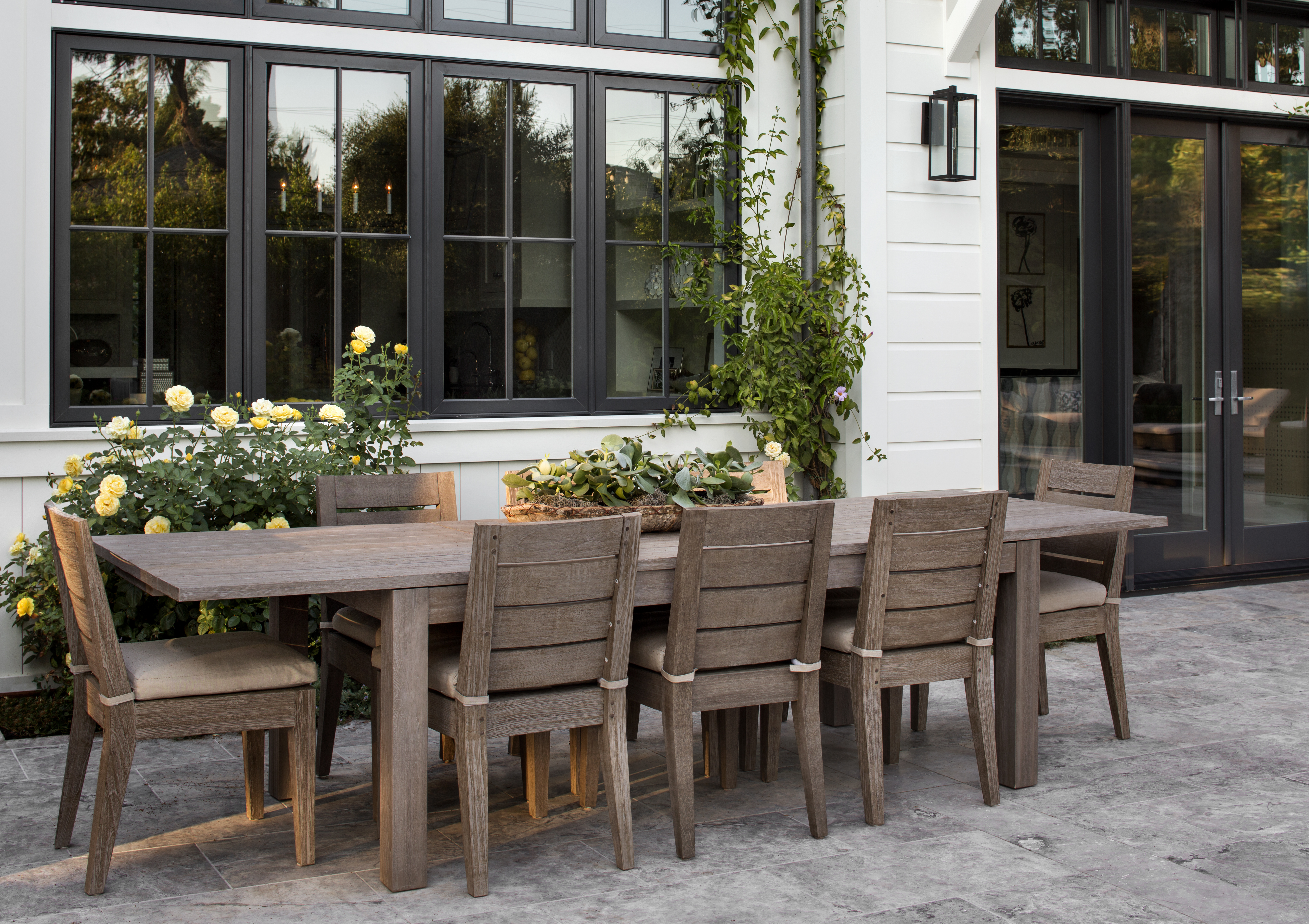 Exit through the glass doors, where you will find a large outdoor dining area. Situated among plants and flowers, the dining table and chairs are made from raw wood.