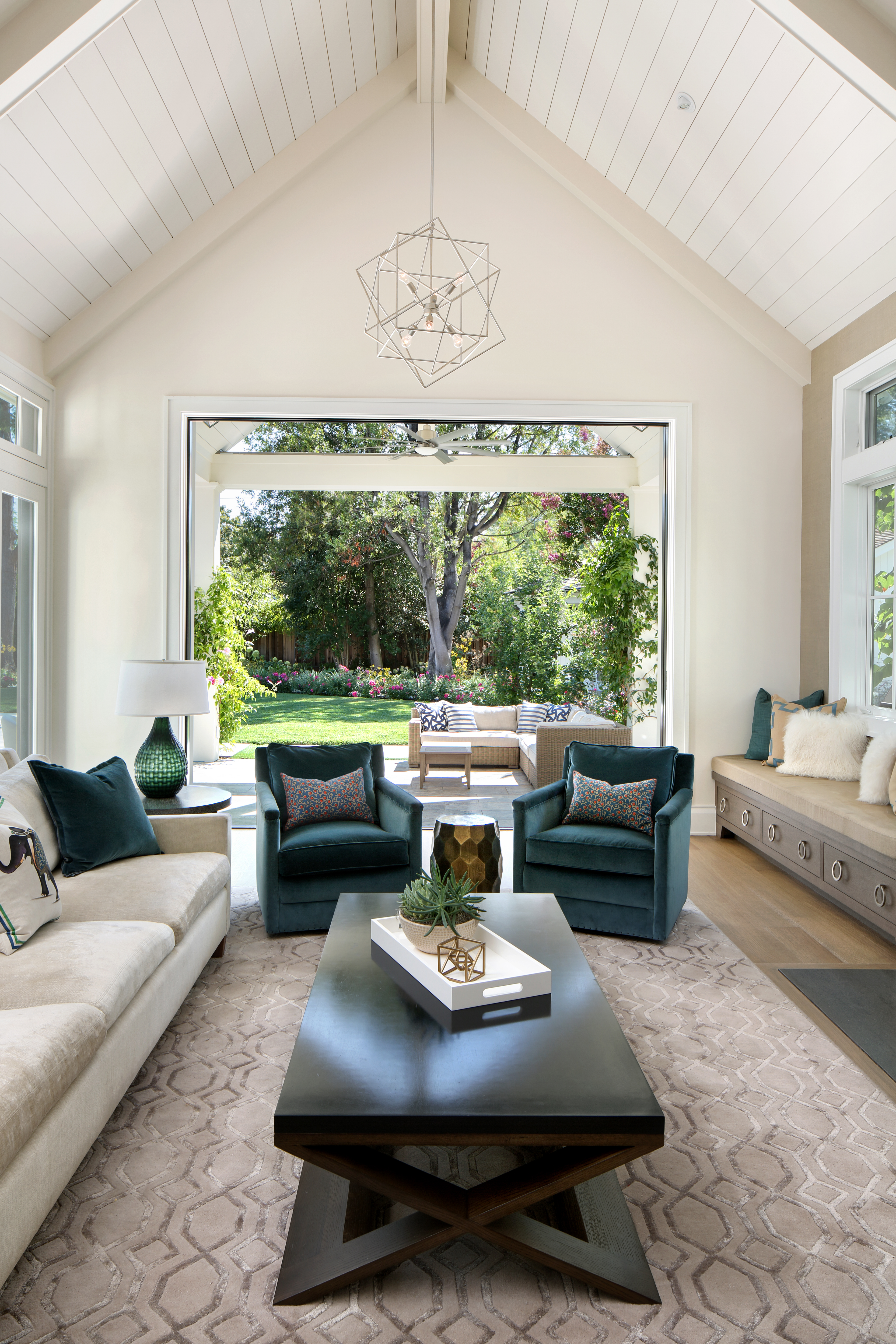 Sophisticated yet striking, this spacious living area features a vaulted ceiling with a caged chandelier. A set of teal armchairs are from Room & Board, the sofa is from Verellen with Kravet fabric, and the custom bench is from Osborn & Little. Pillows by Osborne & Little and Kravet decorate furnishings throughout the space.