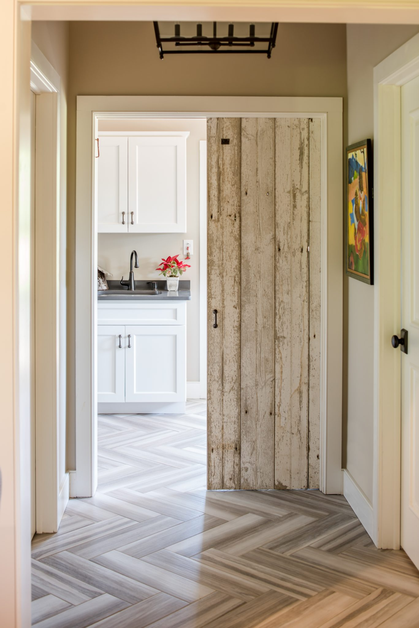 Traditional gray and white mudroom with rustic barn door by Period Architecture
