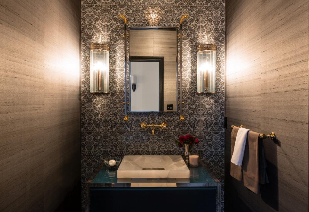 A contemporary powder room with a richly patterned wallpaper and a goldenfaucet and accessories, created byAlisberg Parker Architects.