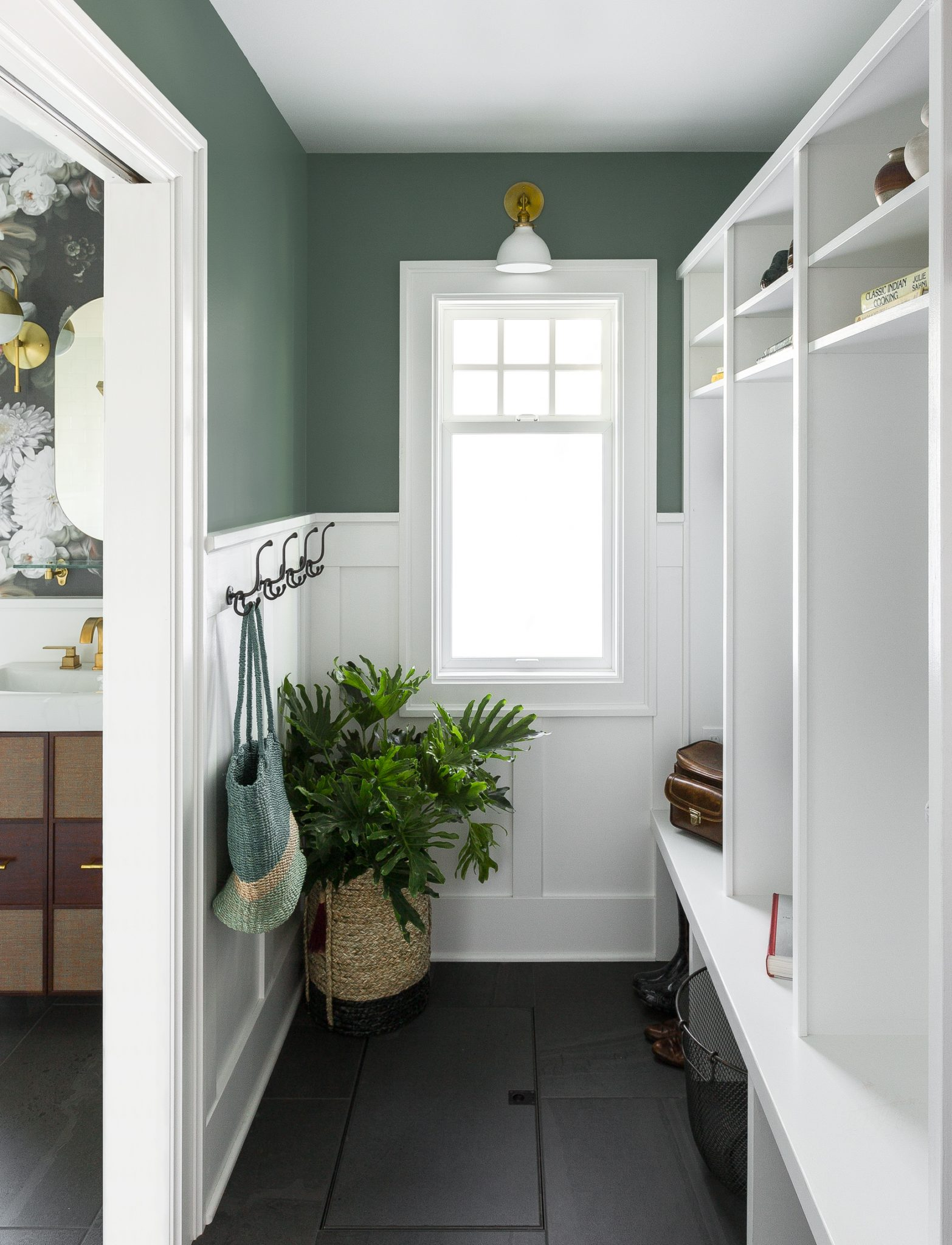 Cool green walls are a unique choice in the mudroom. The contractor, Blue Cabin Builders, constructed the built-in cubbies here, and the wall light is from Schoolhouse.