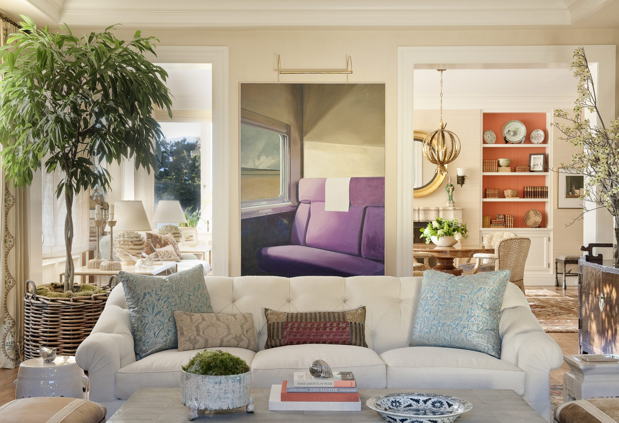 """""""A thoughtful edit is always a good frame of mind while focusing on a handful of items about which you feel strongly,"""" says Tucker. In the home, acolorful oil on canvas calledTrain Seatby John Register brings life to the living room. In front of the painting, thecustom sofa designed by Tucker & Marks is upholstered in a cotton-blend fabric from Rogers & Goffigon with tape trim by Samuel & Sons. The blue-and-gold pillows decorating the sofa add a chic baroque note to the decor; thefabric is from Fortuny and the fan-edge trim, Samuel & Sons."""