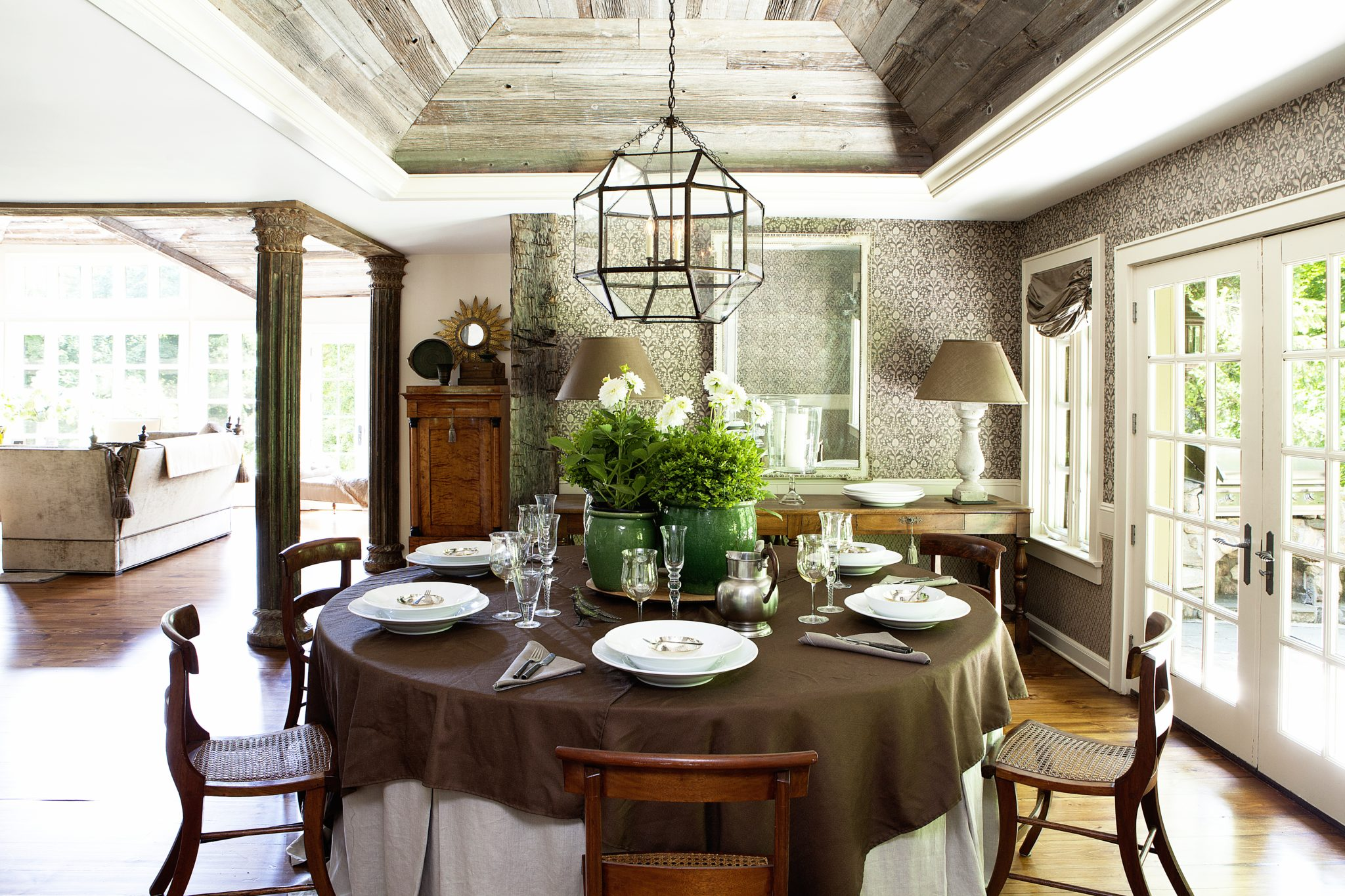 Table set for entertaining & outdoor pots filled with greenery. by Laura Michaels Design